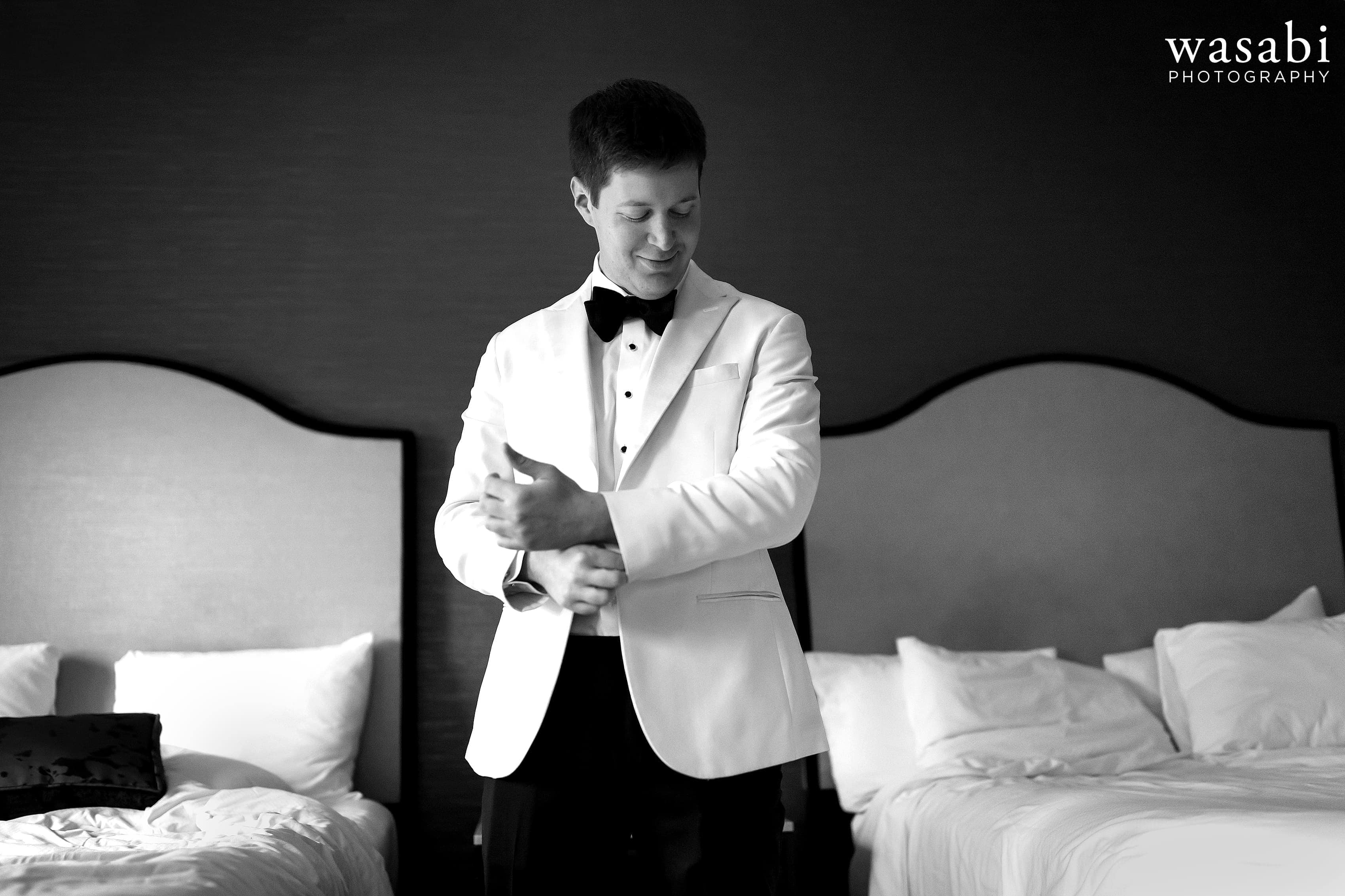 Groom adjusts his jacket while getting ready for wedding at InterContinental Chicago Magnificent Mile Hotel