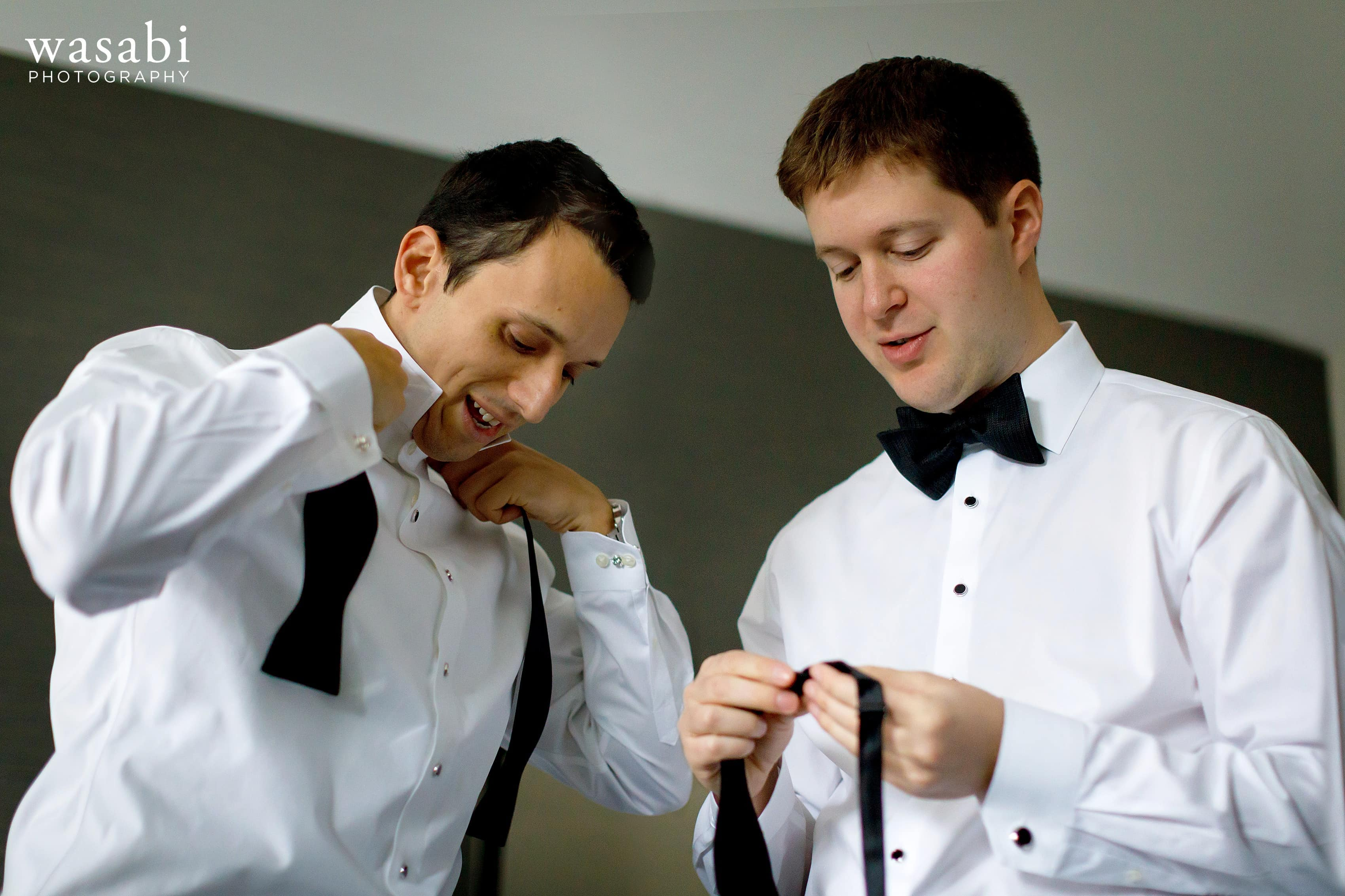 Groom and best man put on their ties while getting ready for wedding at InterContinental Chicago Magnificent Mile Hotel