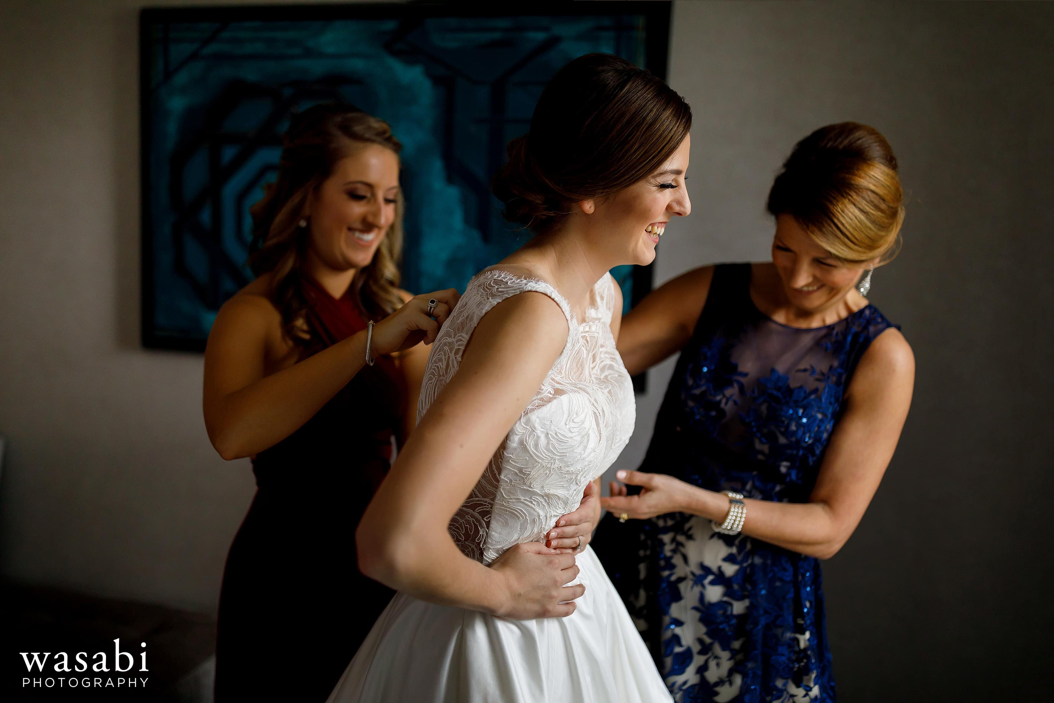 Mom and sister help bride into dress in the presidential suite while getting ready for wedding at InterContinental Chicago Magnificent Mile Hotel
