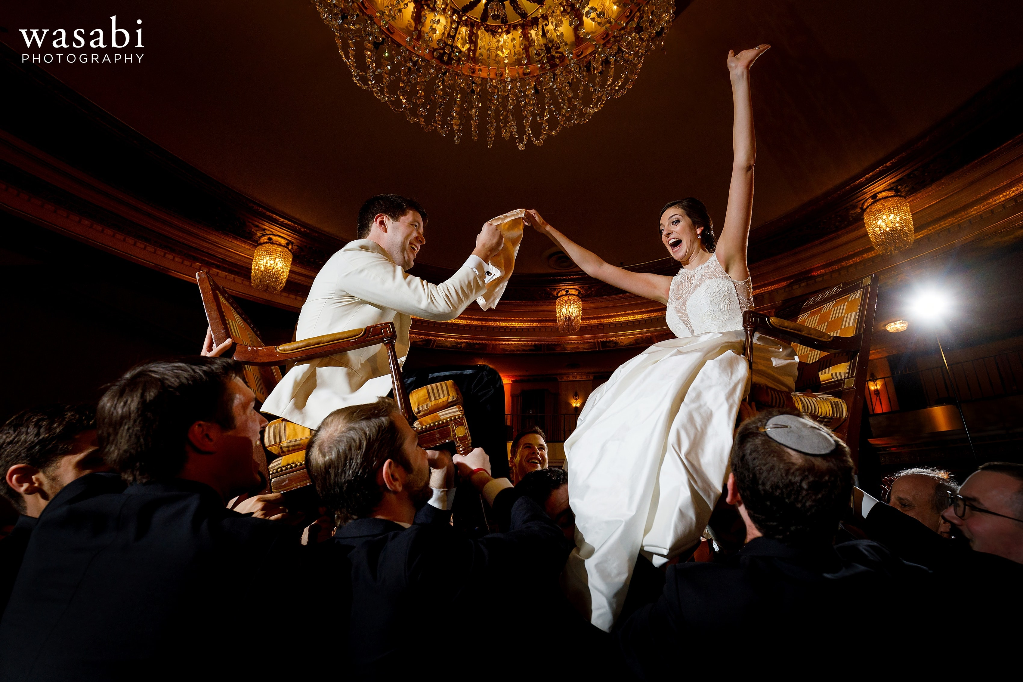 bride and groom are lifted onto chairs during the Horah during Jewish wedding reception at InterContinental Chicago Magnificent Mile Hotel