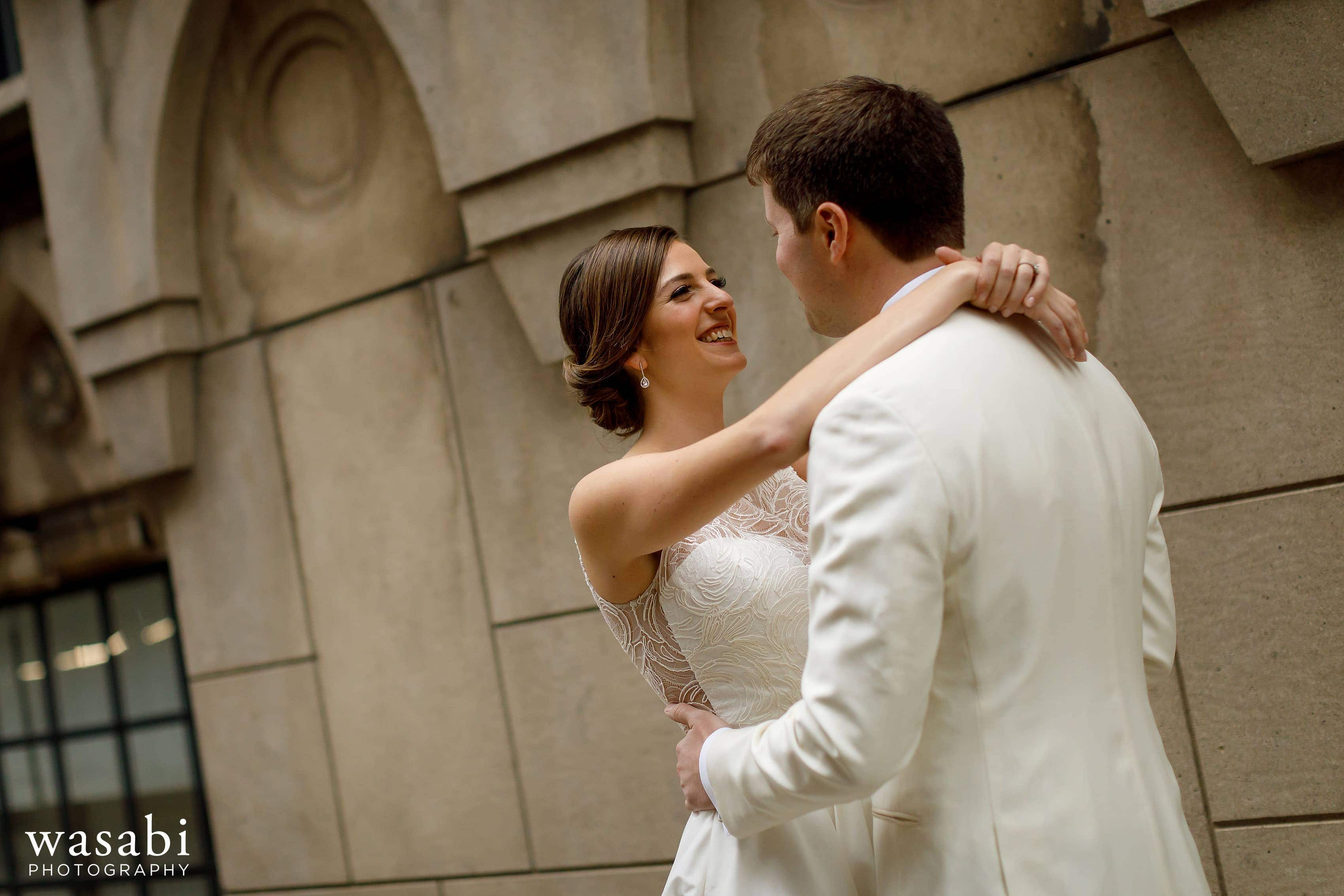 bride and groom hug during first look outside of InterContinental Chicago Magnificent Mile Hotel