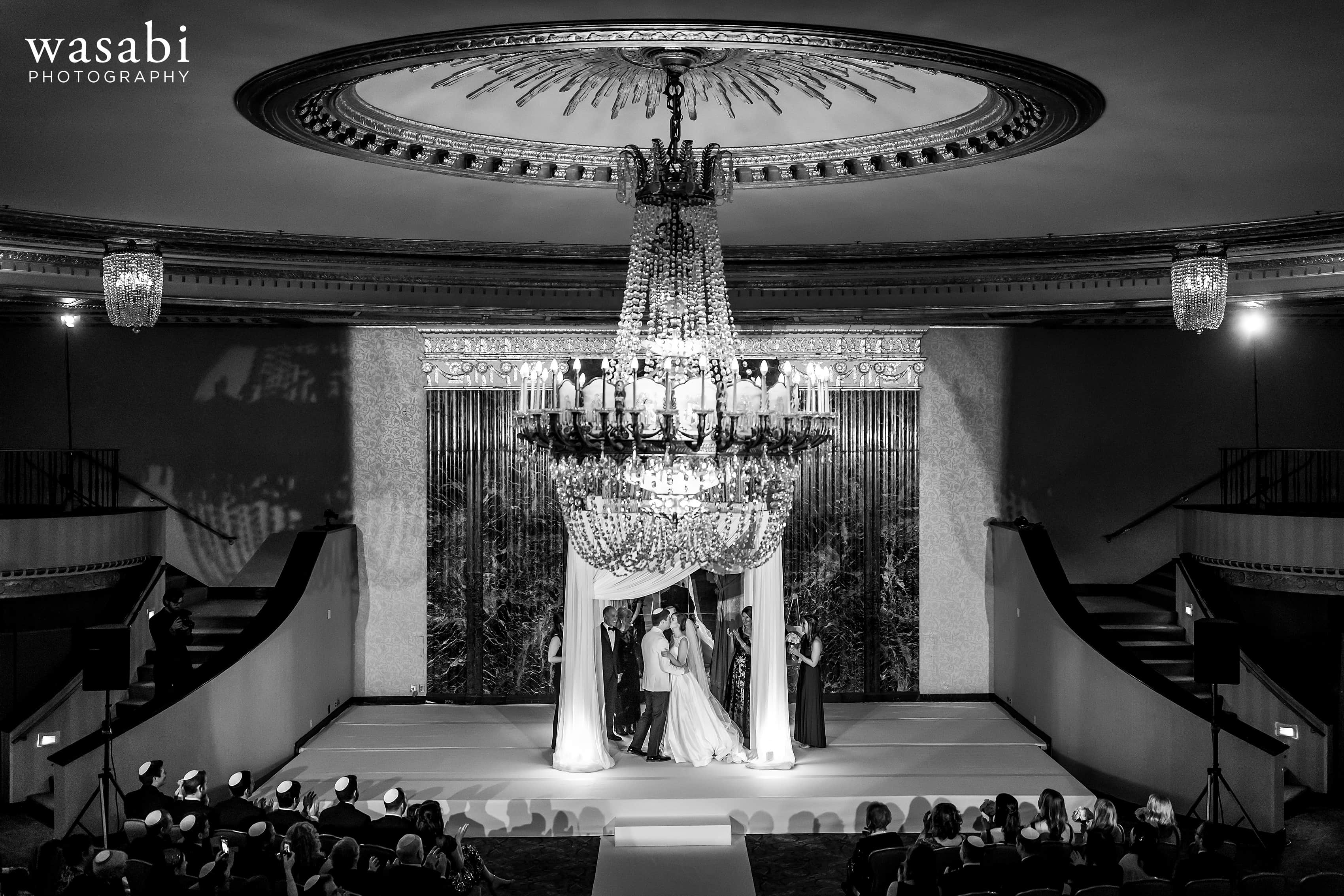 bride and groom kiss at the end of Jewish wedding ceremony at InterContinental Chicago Magnificent Mile Hotel