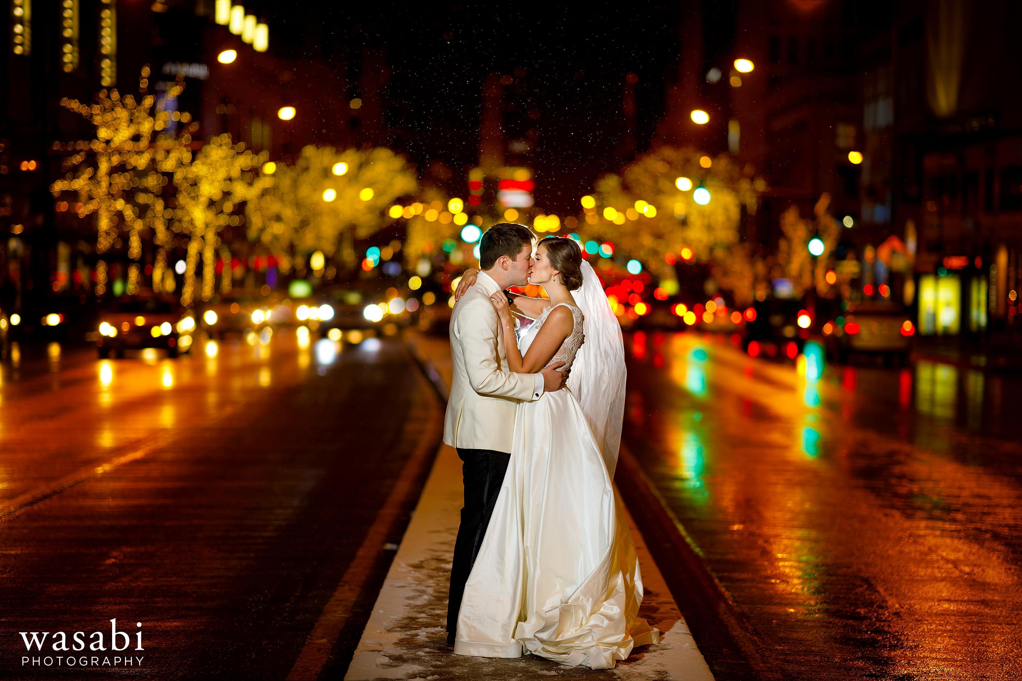 bride and groom kiss in the median on Michigan Ave. in downtown Chicago with snow coming down during winter Jewish Wedding