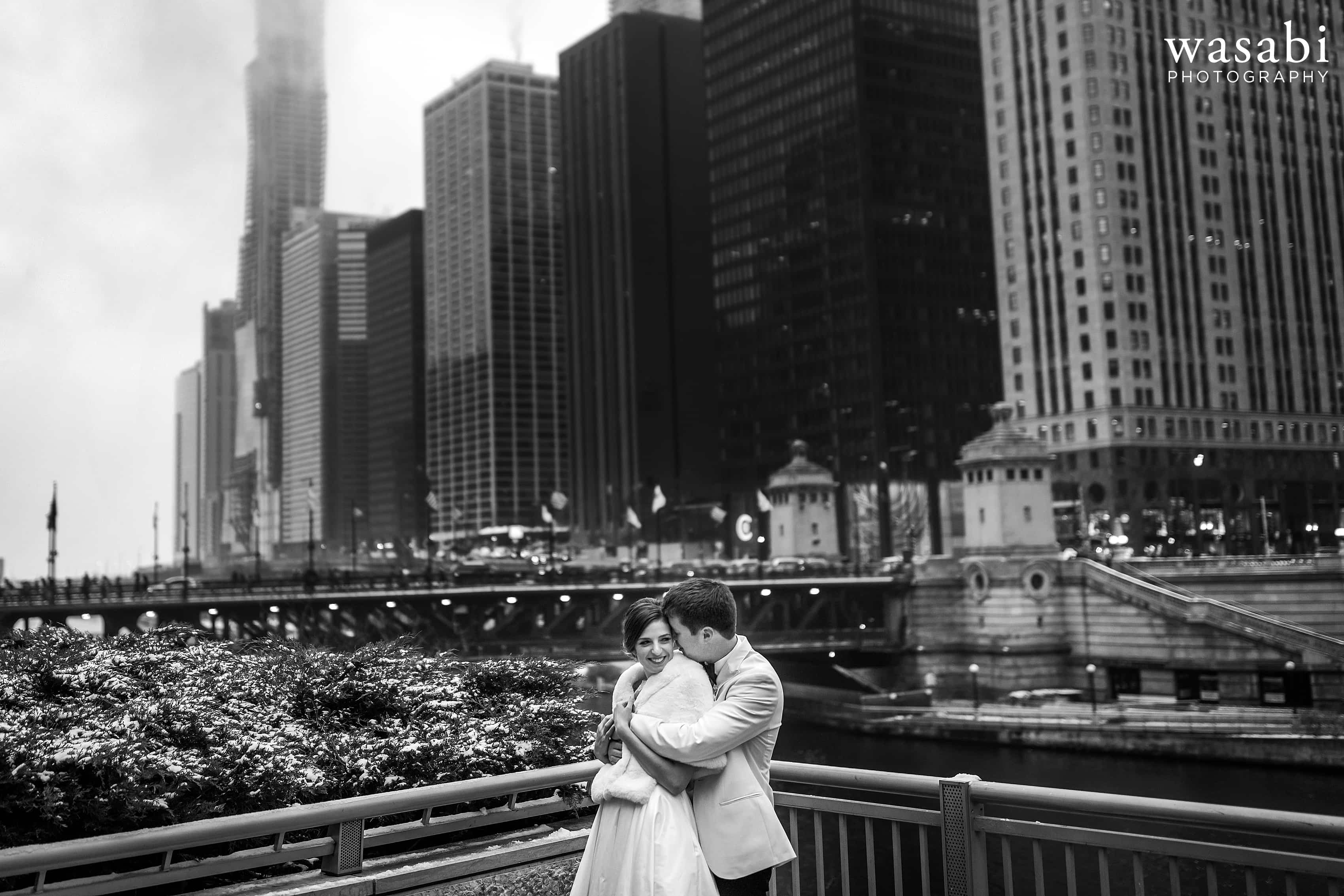 bride and groom pose for a portrait with Chicago skyline and riverwalk in the background during wedding portraits in downtown Chicago