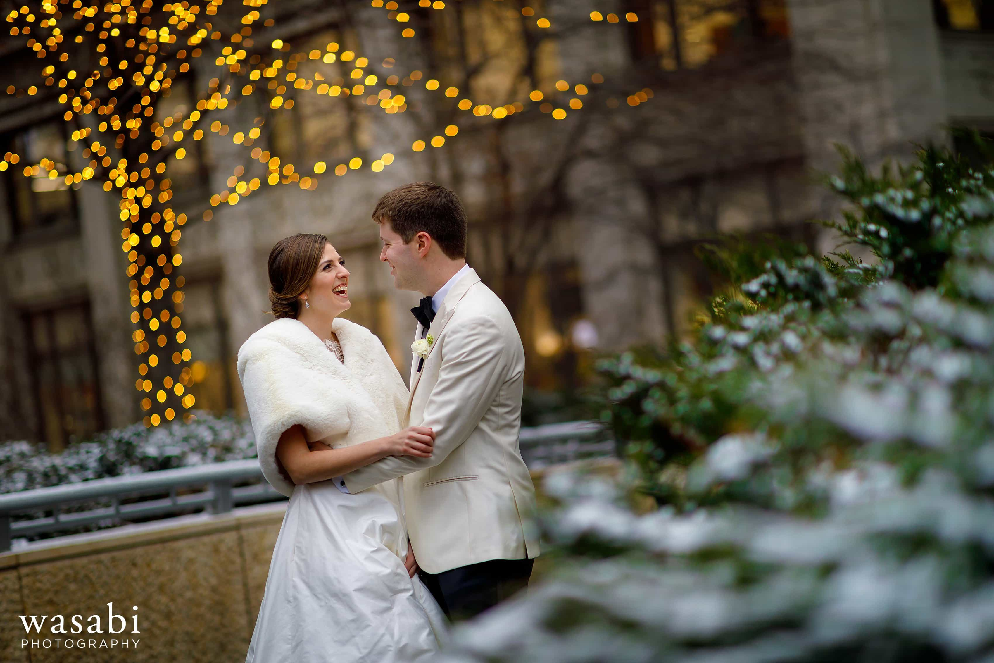 bride and groom pose for a portrait with lights in the background and snow covered tree in the foreground during wedding portraits in downtown Chicago