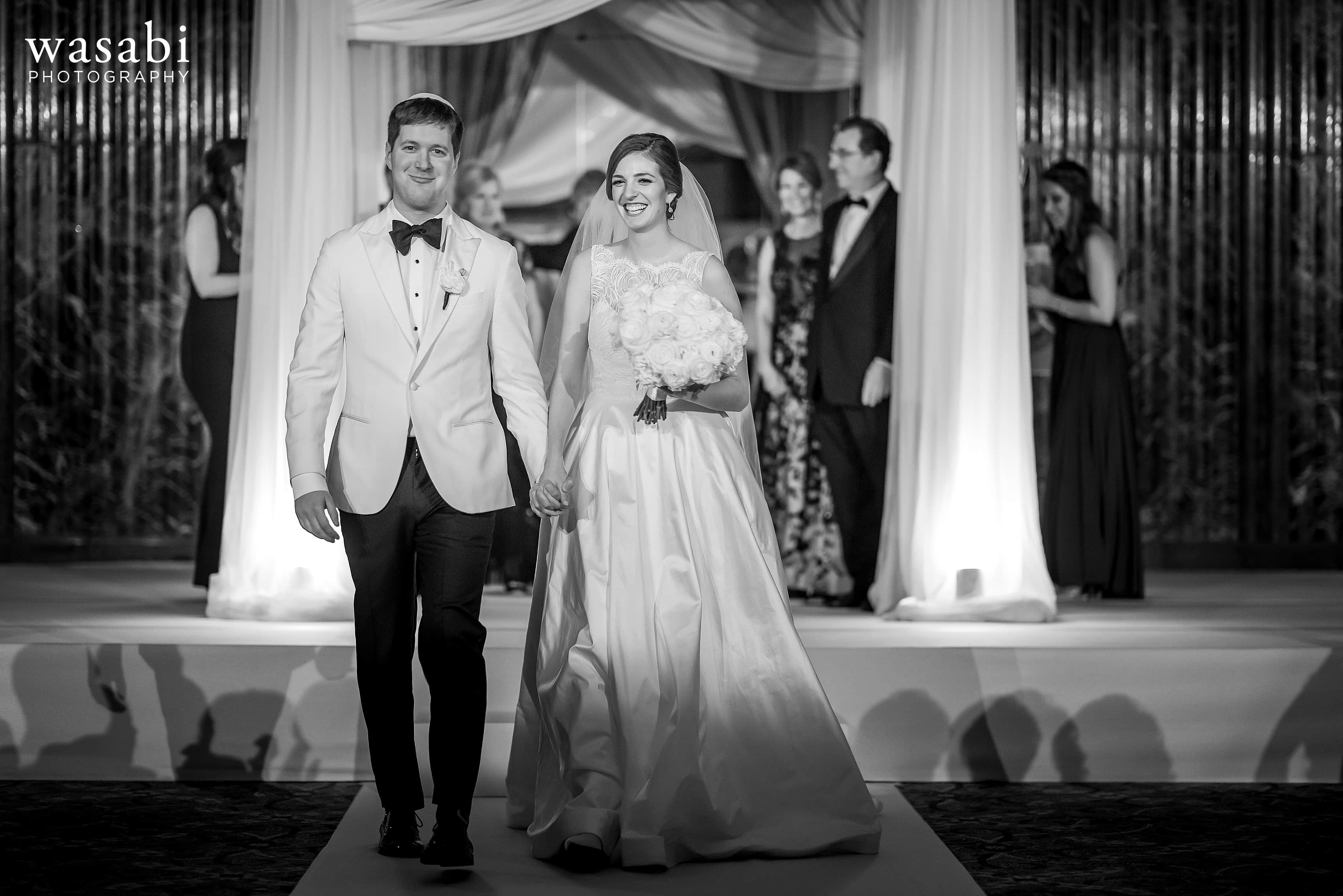 bride and groom walk back down the aisle together at the end of Jewish wedding ceremony at InterContinental Chicago Magnificent Mile Hotel