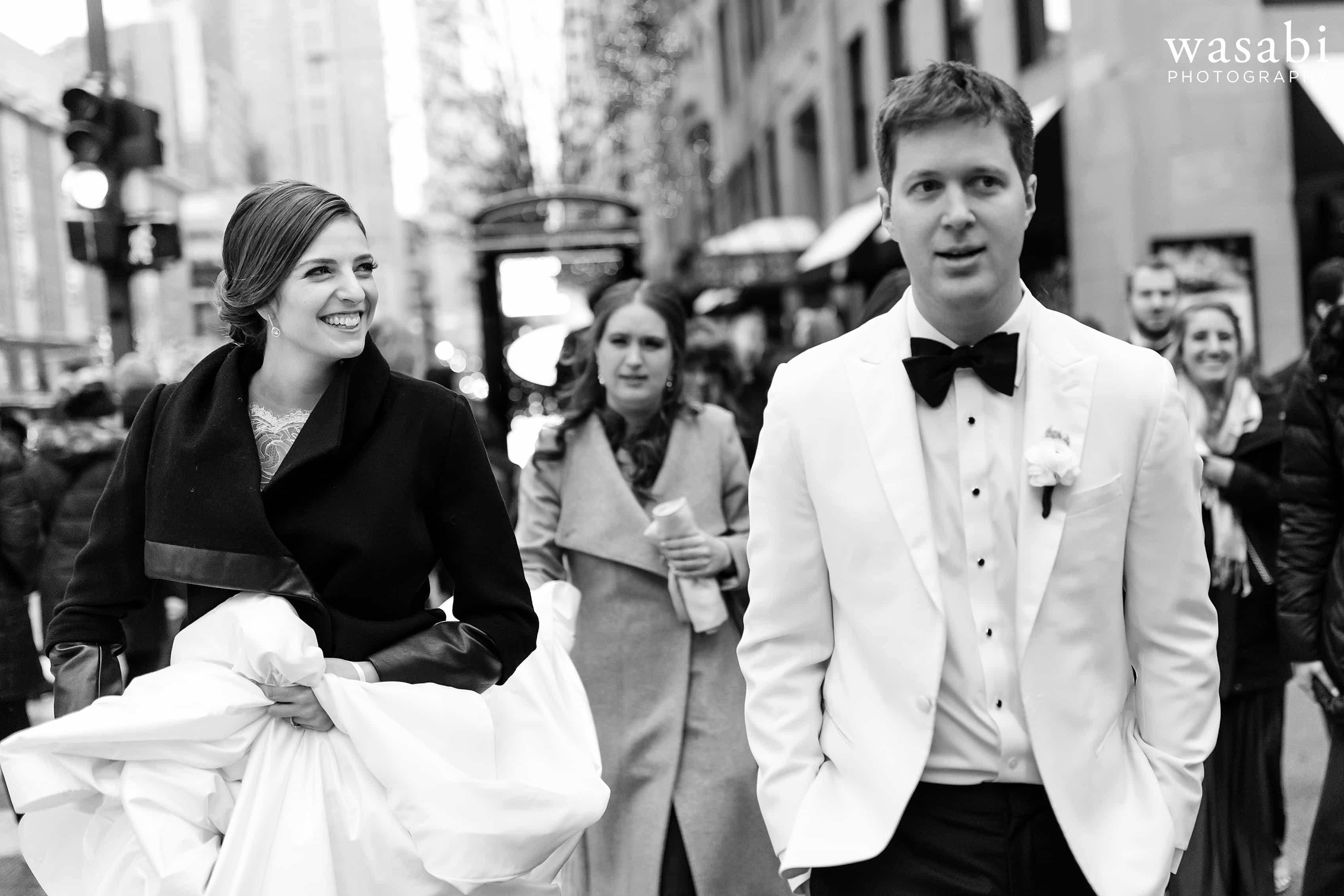 bride and groom walk down Michigan Ave. in downtown Chicago during wedding portraits