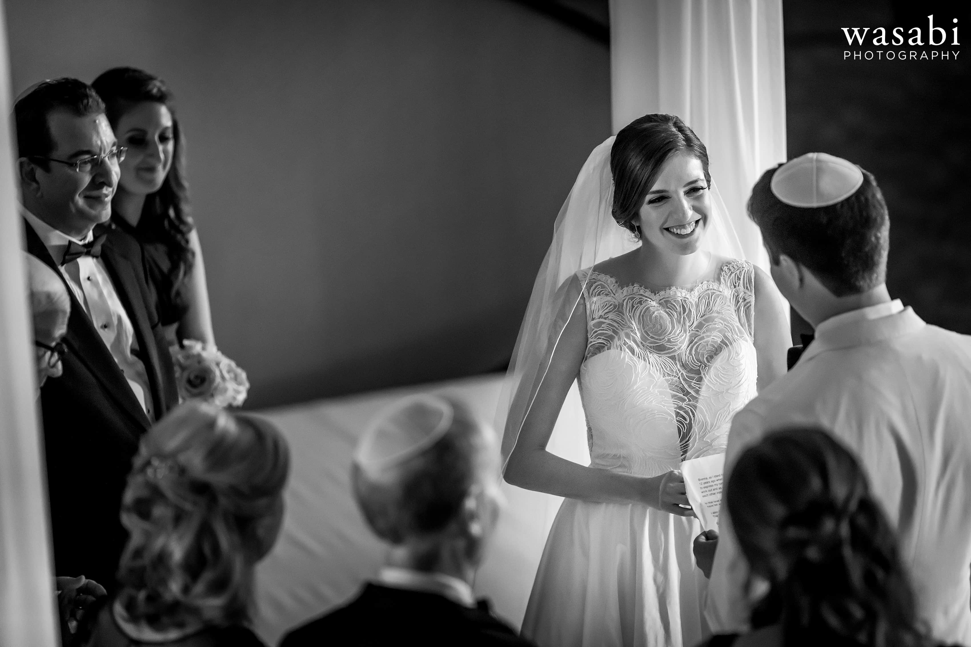 bride smiles at groom during Jewish wedding ceremony at InterContinental Chicago Magnificent Mile Hotel