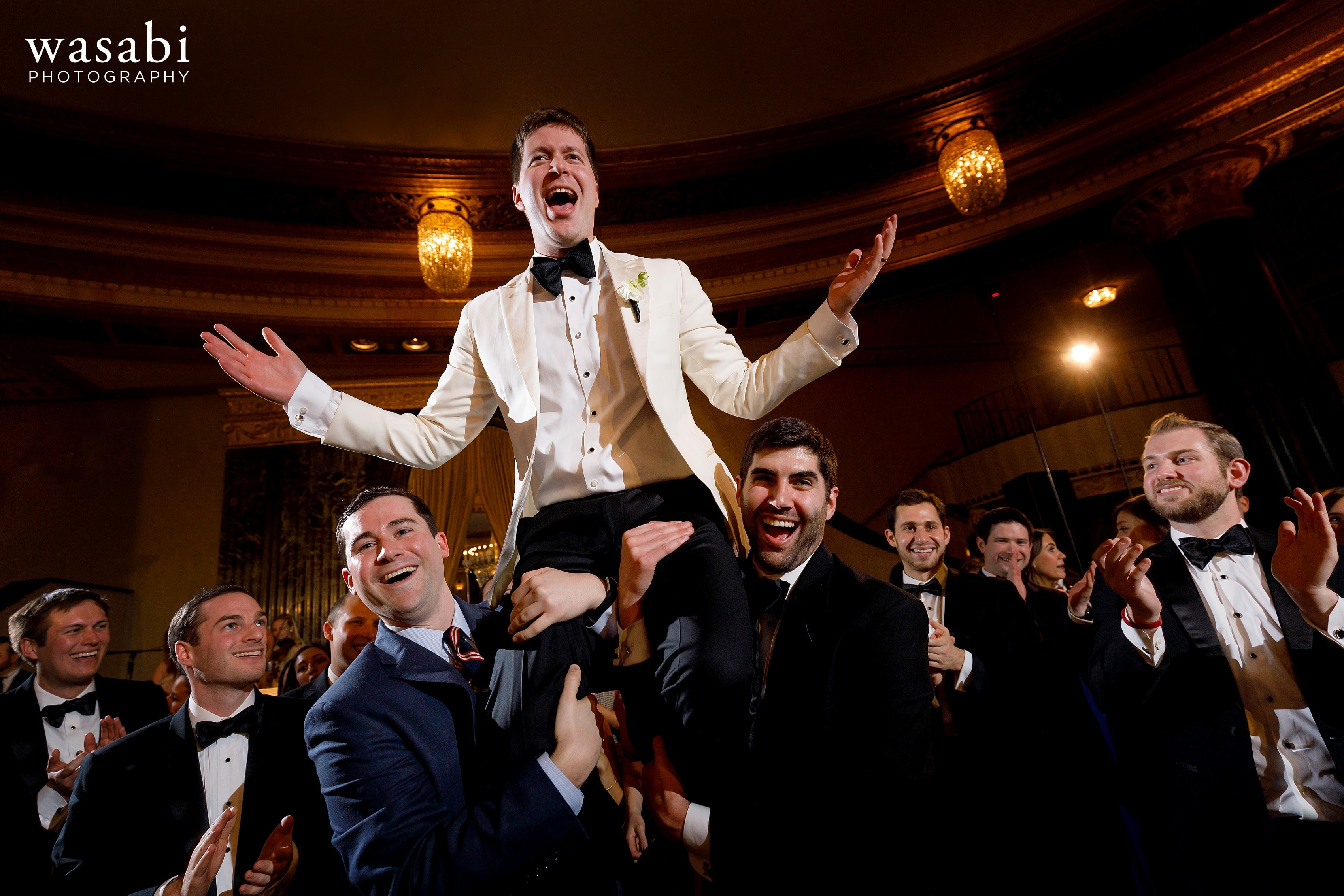 groom is lifted up by friends during Jewish wedding reception at InterContinental Chicago Magnificent Mile Hotel