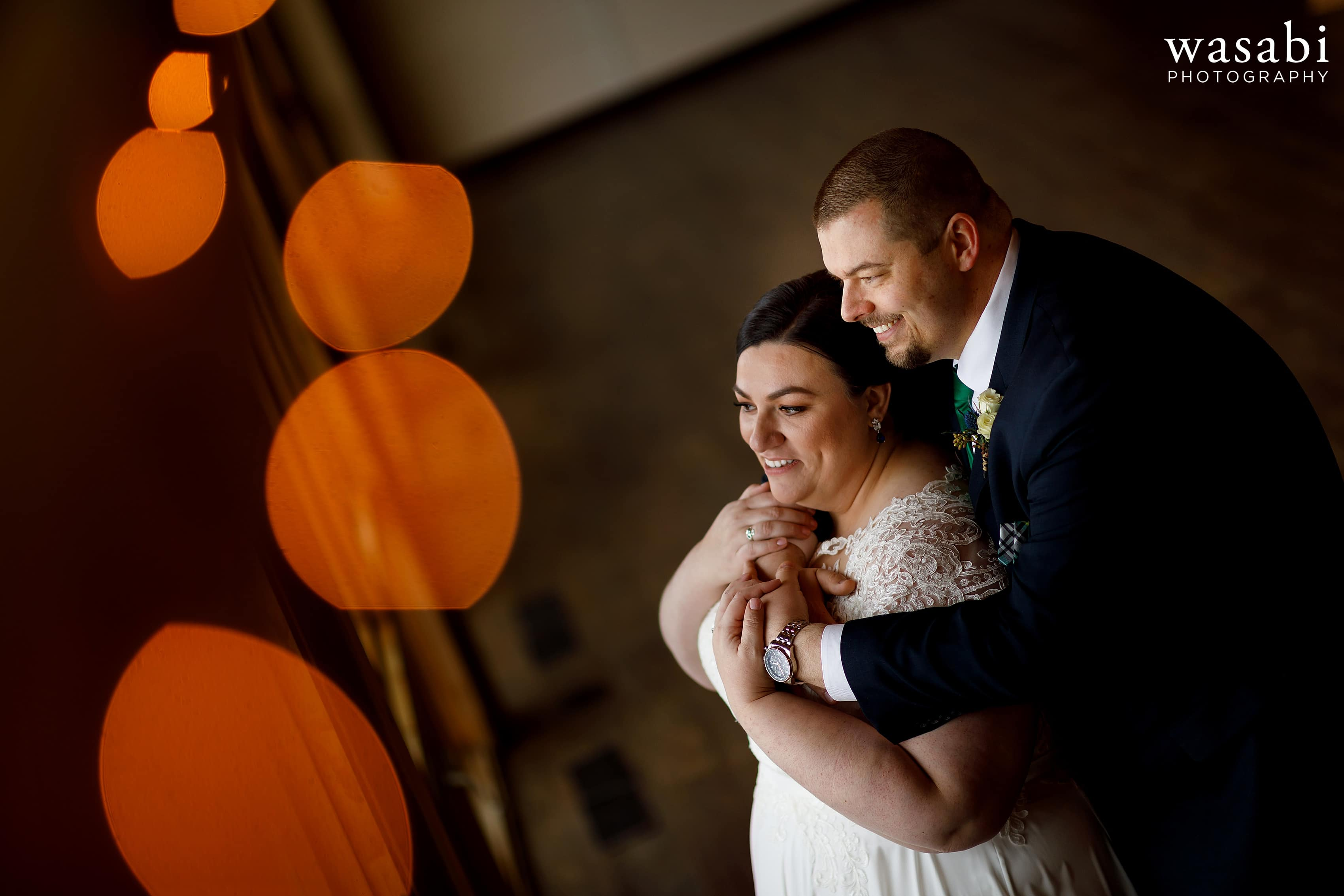 bride and groom pose for portrait with bokeh lights in foreground