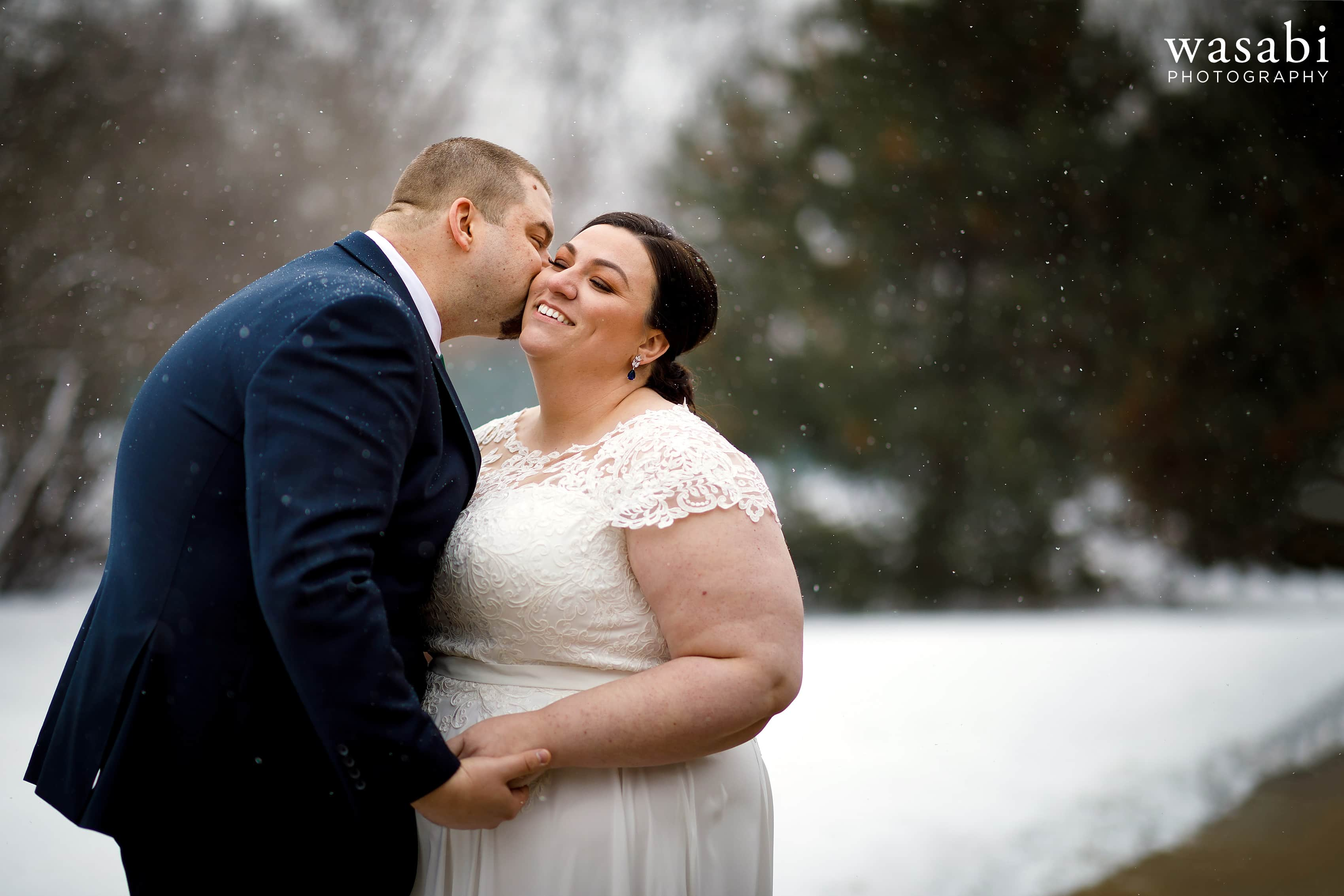 bride and groom pose for wedding portrait with snow coming down around them