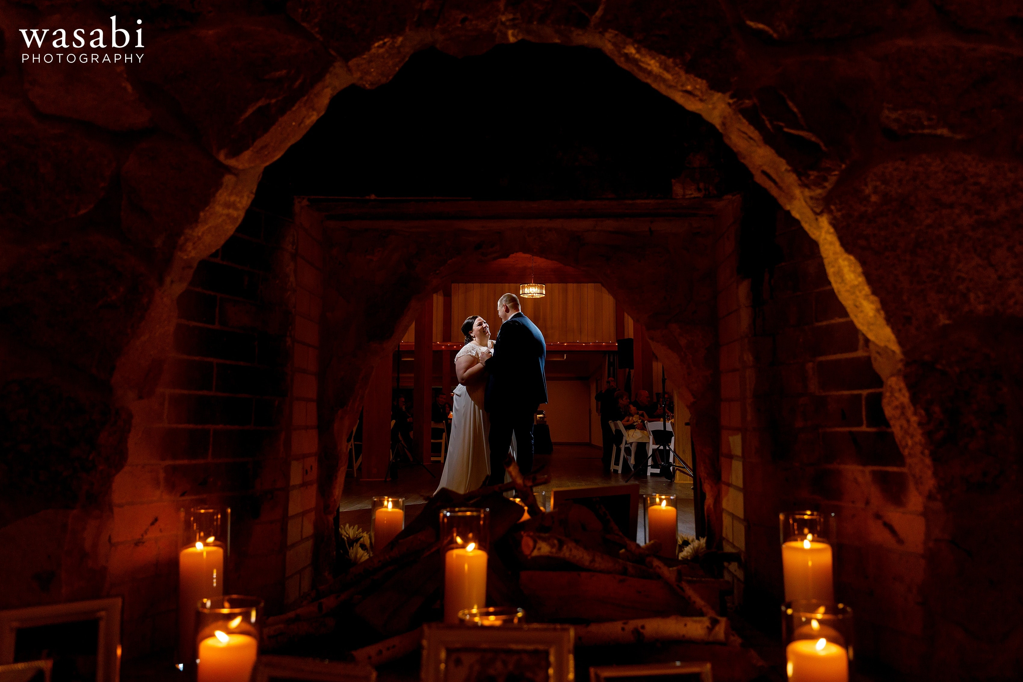 bride and groom share first dance with view through fireplace and candles in the foreground during Oak Brook Bath and Tennis Club wedding reception