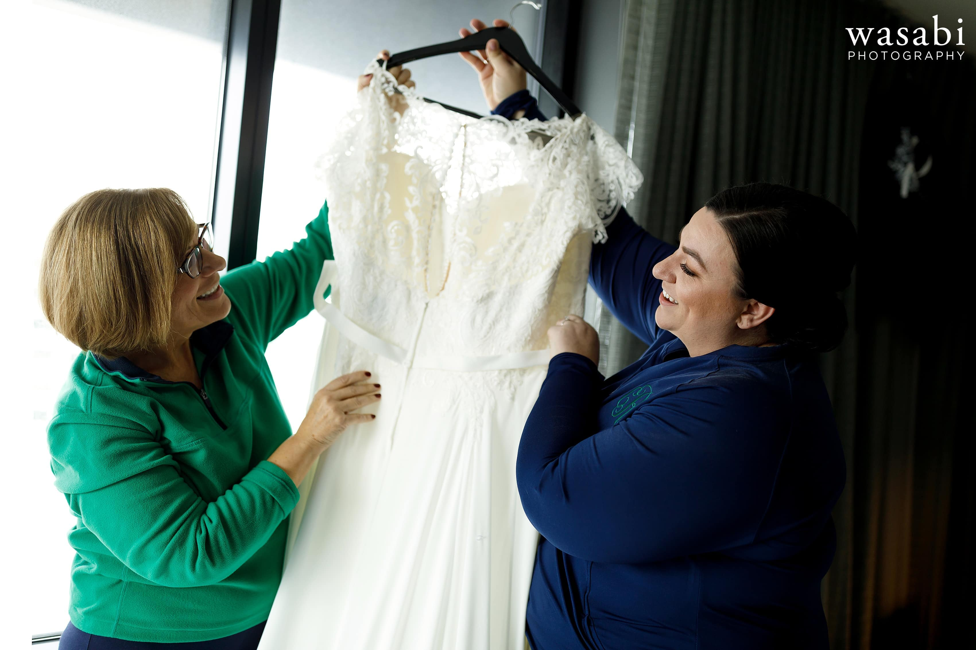 bride and mother look at wedding dress before putting on the dress for wedding