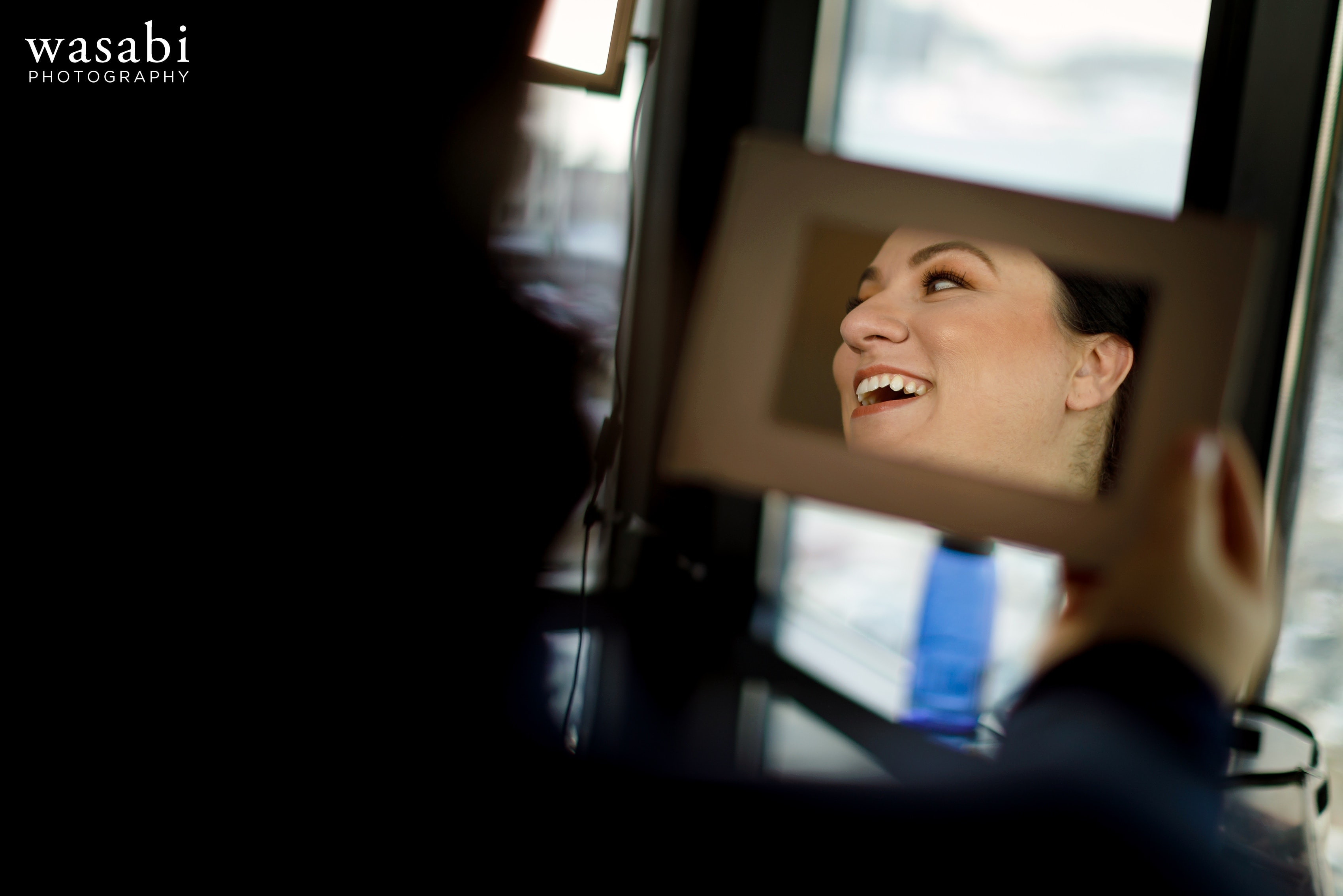 bride laughs in mirror reflection while having her makeup done before her wedding