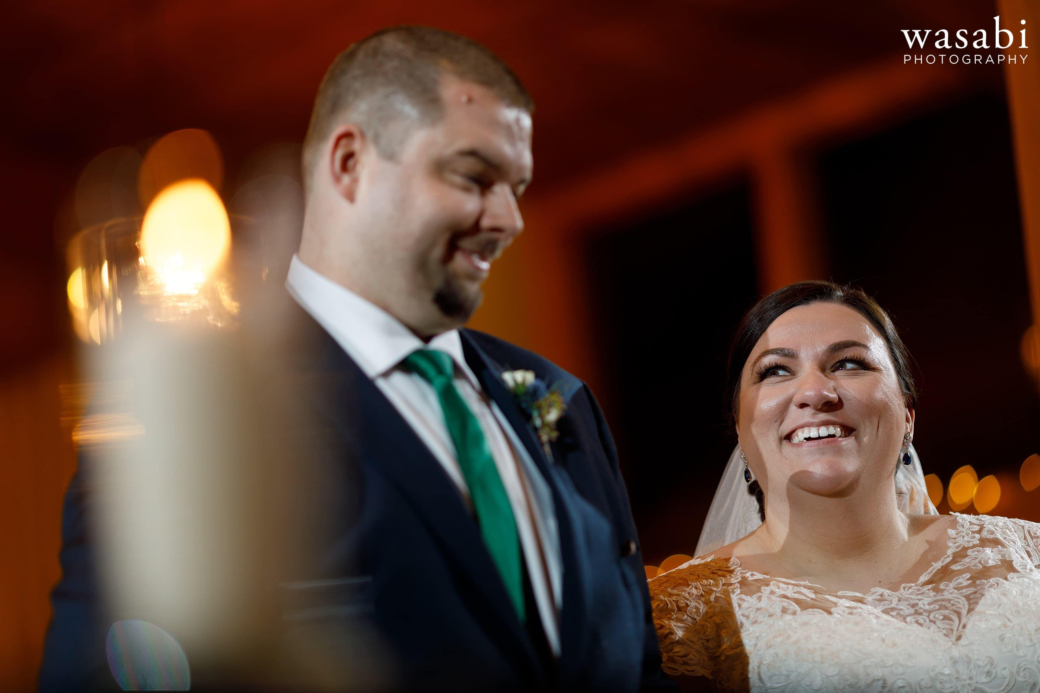 bride smiles at groom during Oak Brook Bath and Tennis Club wedding ceremony
