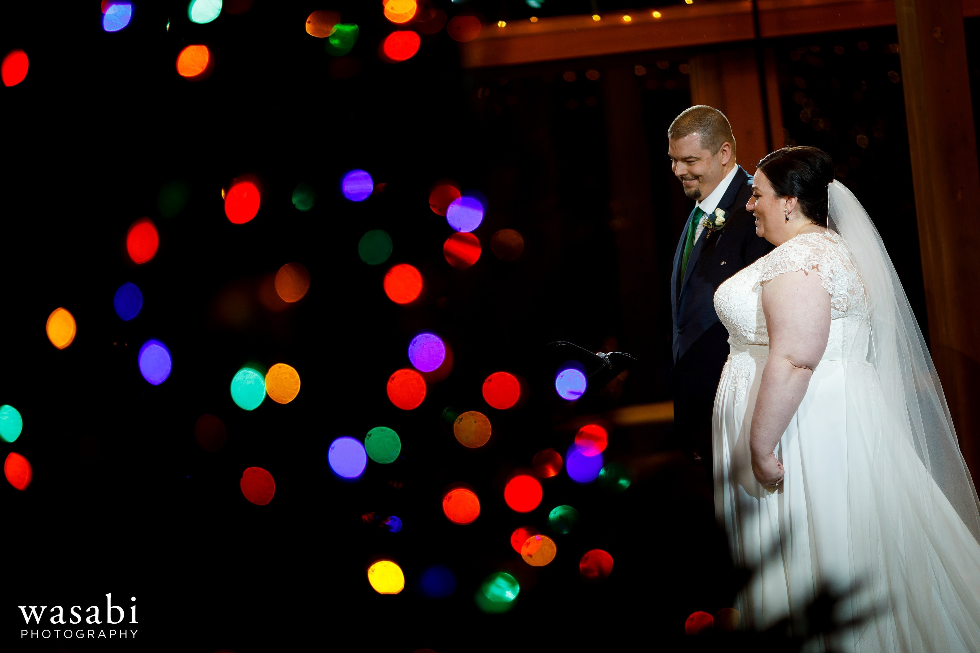 colored Christmas tree lights in the foreground and bride and groom at the the alter during Oak Brook Bath and Tennis Club wedding ceremony