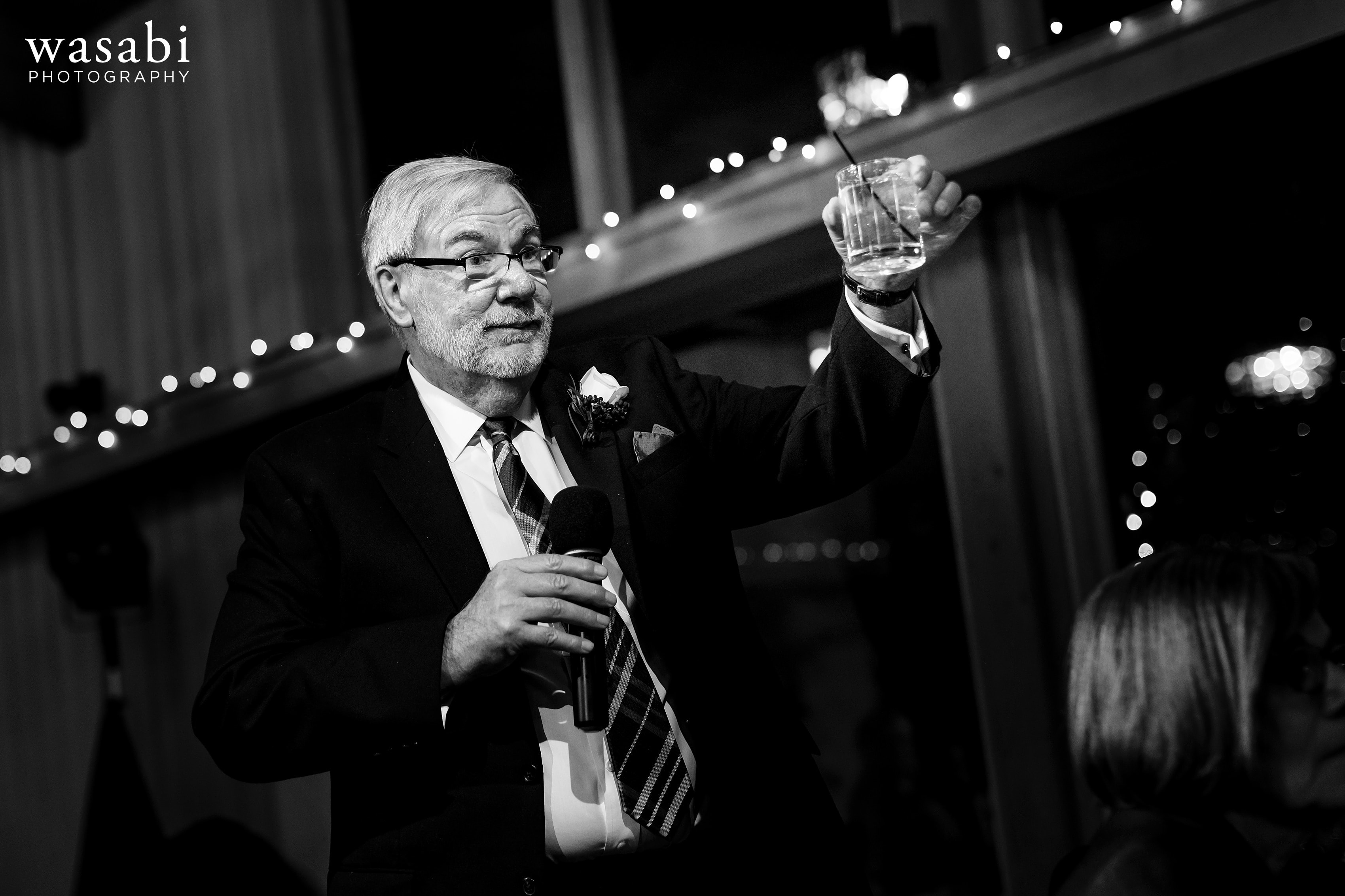 father of the bride toasts couple during wedding reception