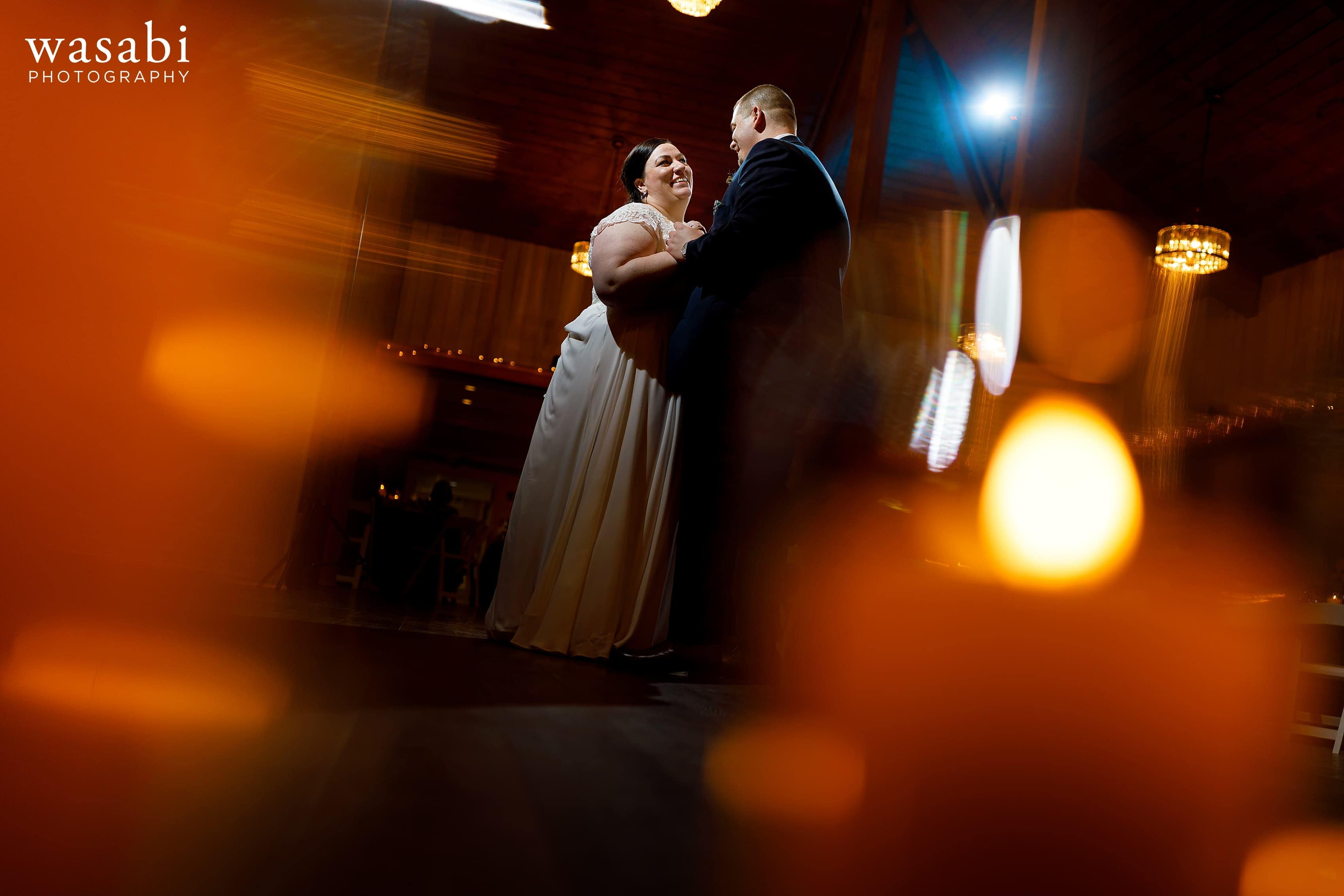 first dance photo with candle light bokeh in the foreground during Oak Brook Bath and Tennis Club wedding reception