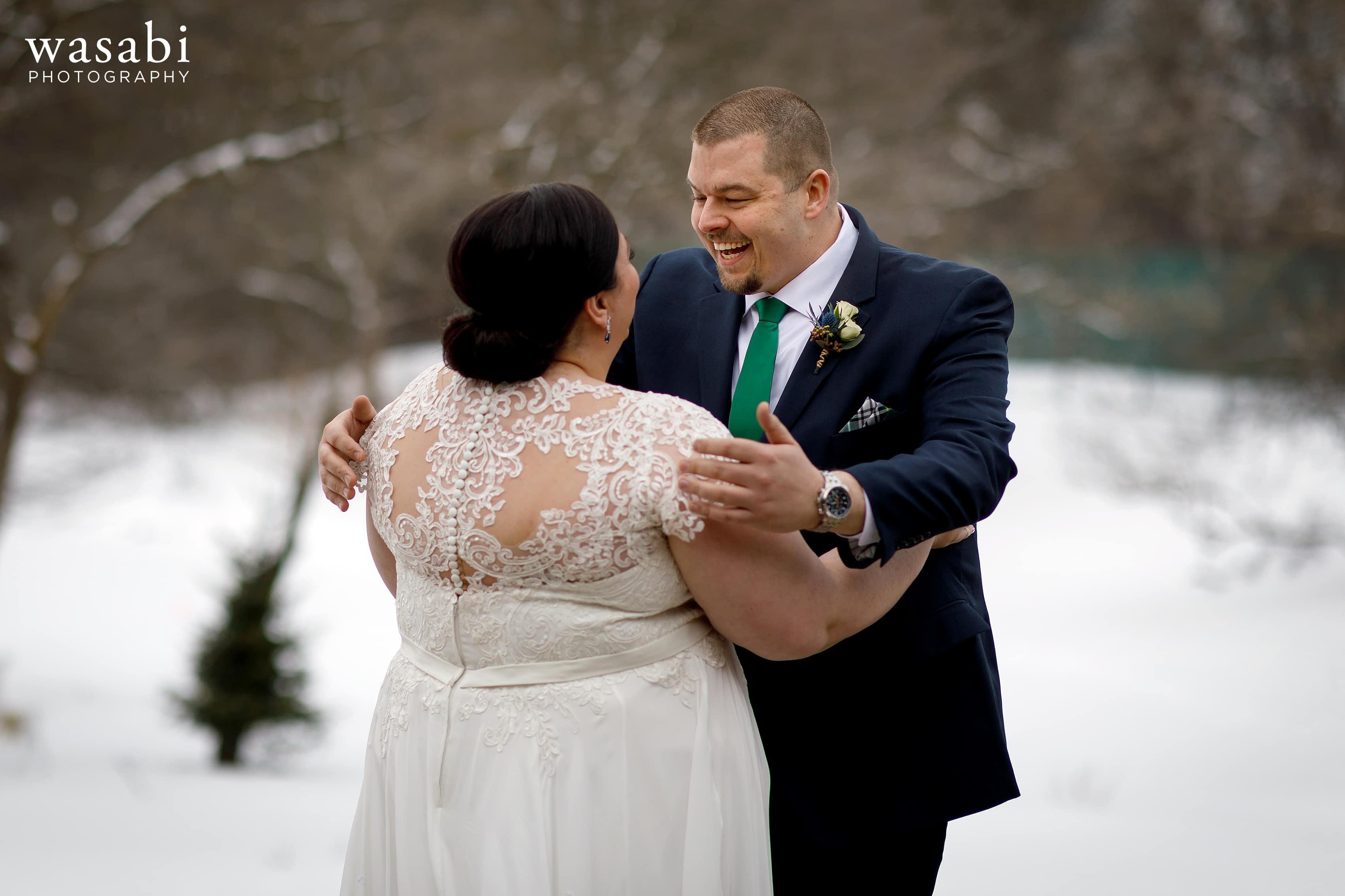 groom reacts to seeing bride for the first time during a first look with snow in the background