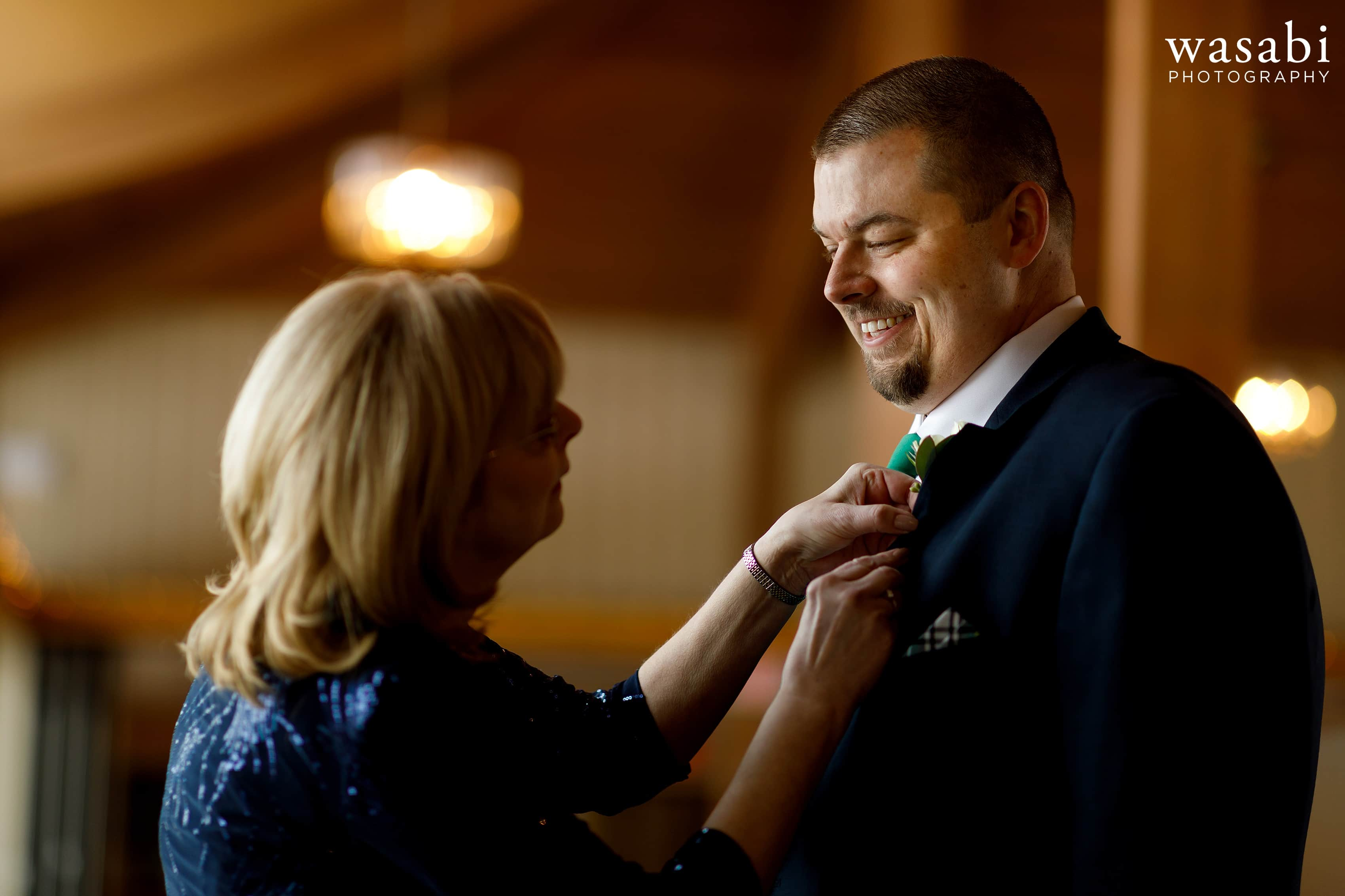 mother of groom puts boutonnière on son's jacket while getting ready for wedding
