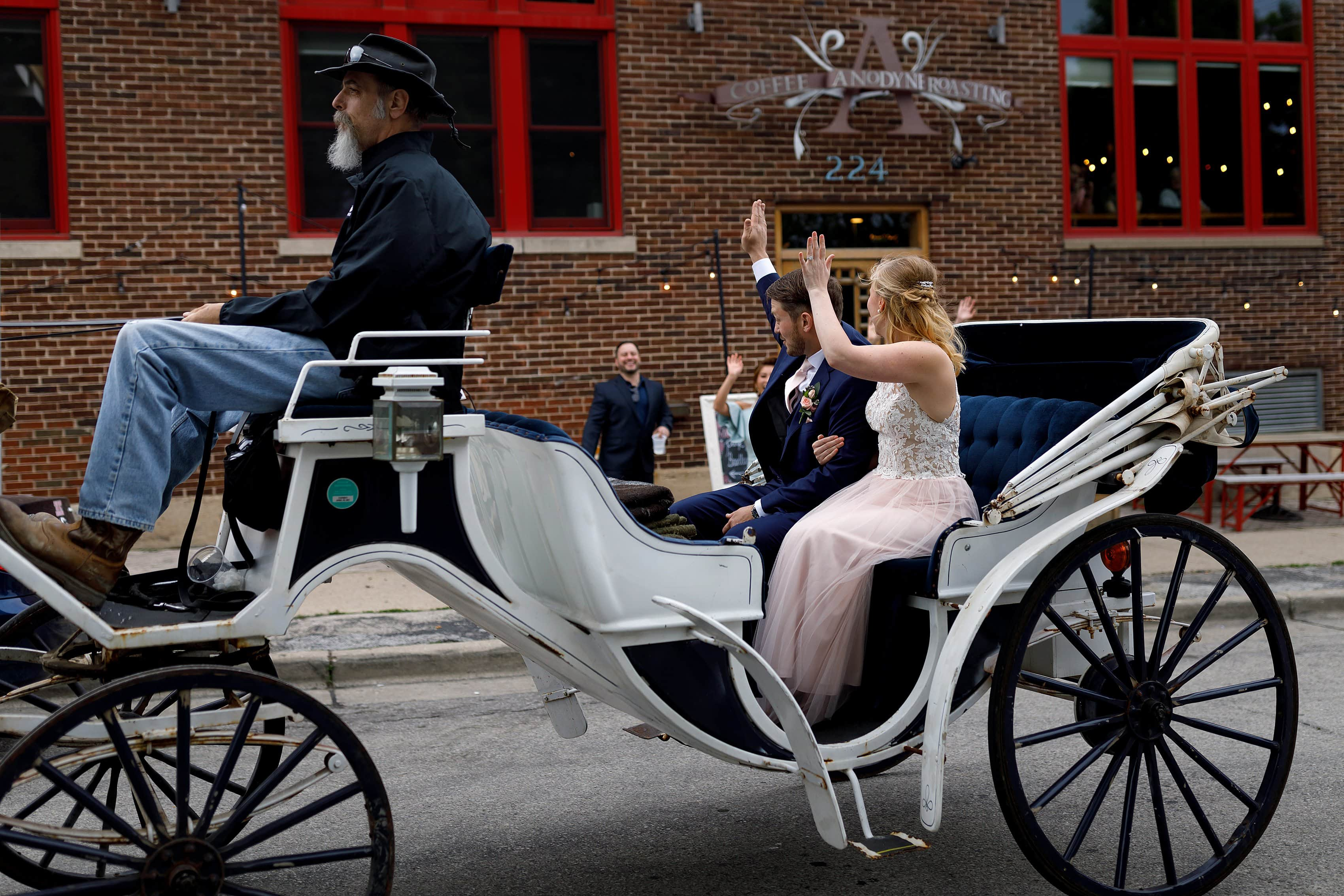 Couple waves to guests outside Anodyne coffee roasting co. in Milwaukee Wisconsin after their wedding ceremony