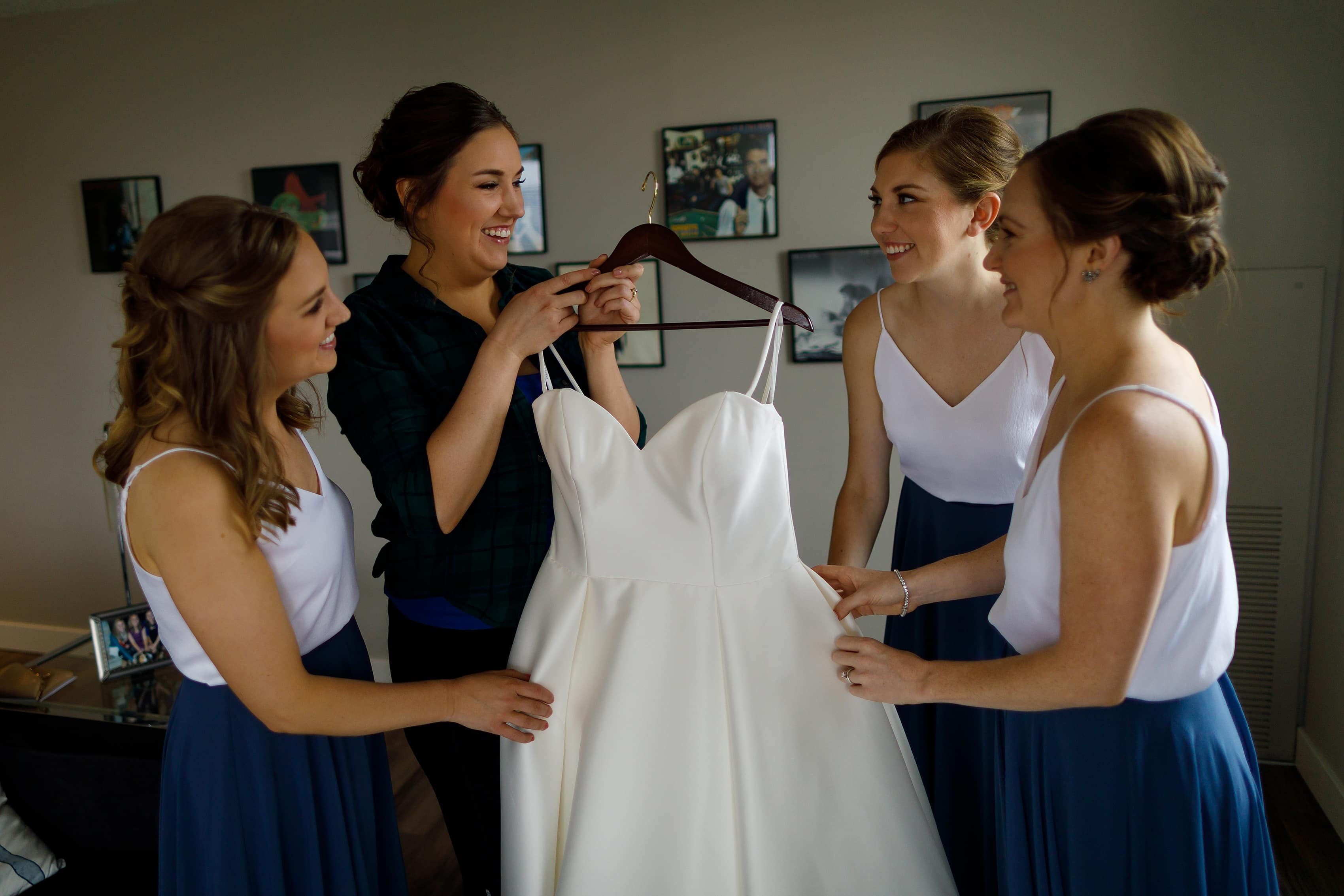 bride and bridesmaids hold wedding dress