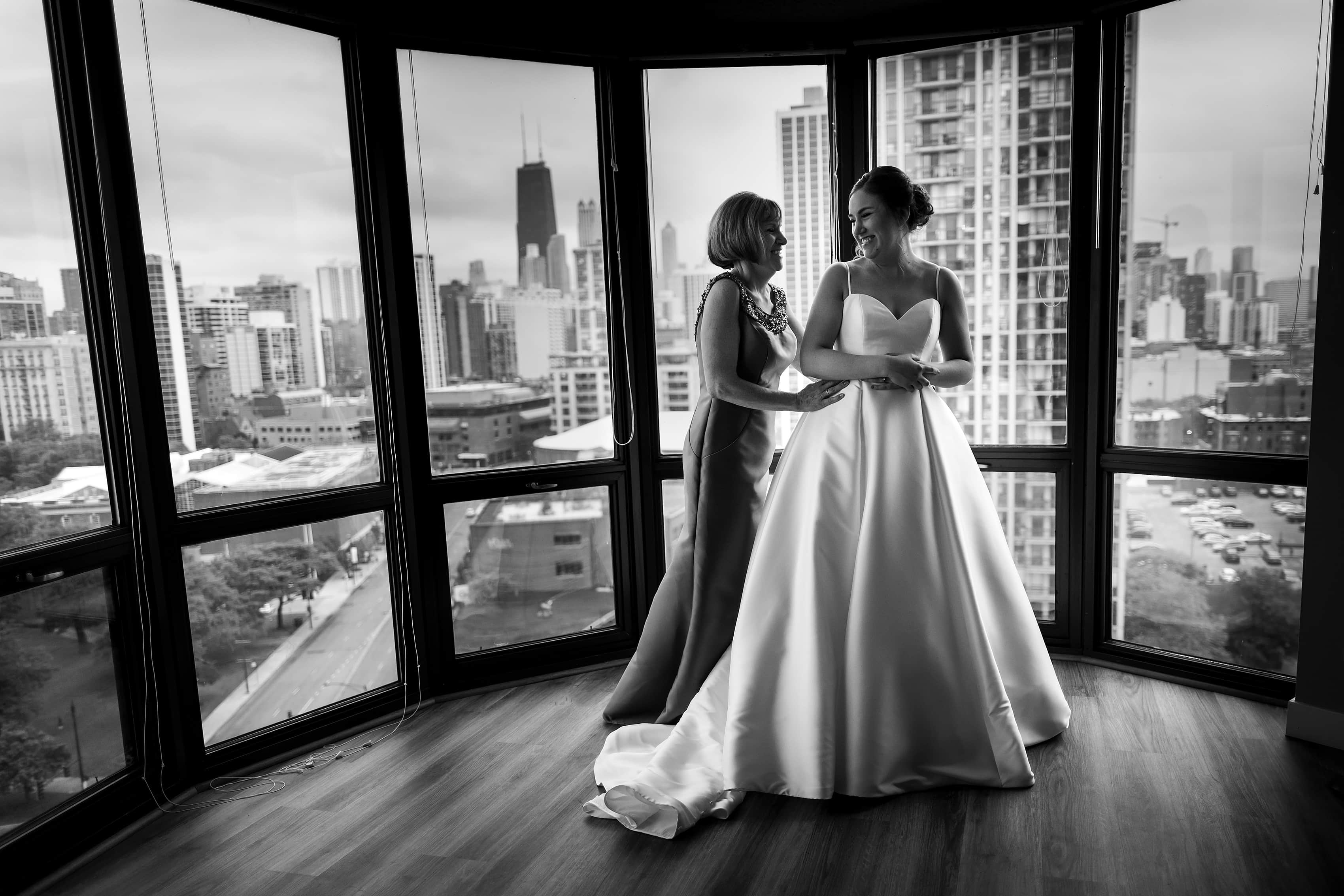 bride and mother get ready for wedding after putting on the dress