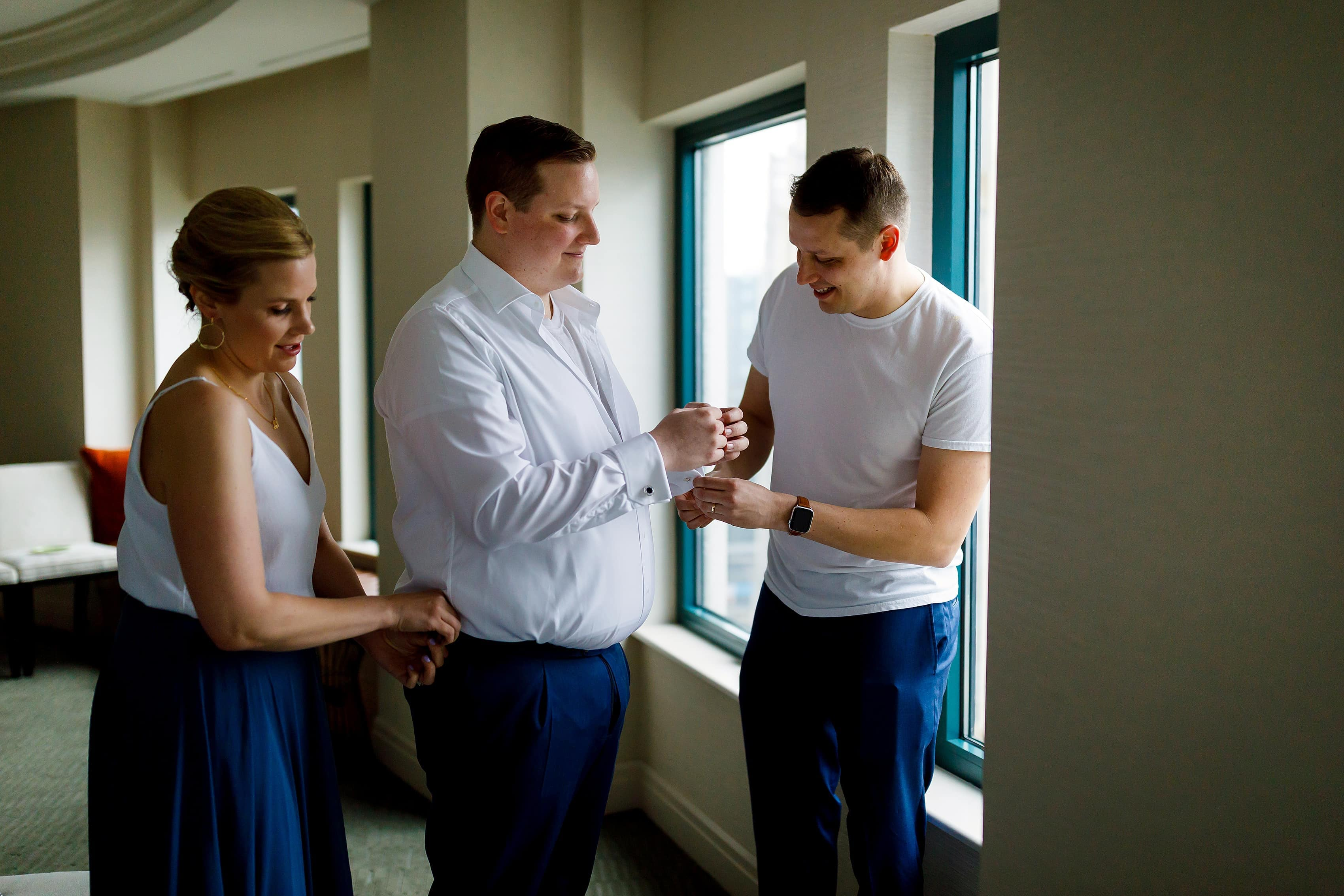 groom gets ready with his siblings for wedding