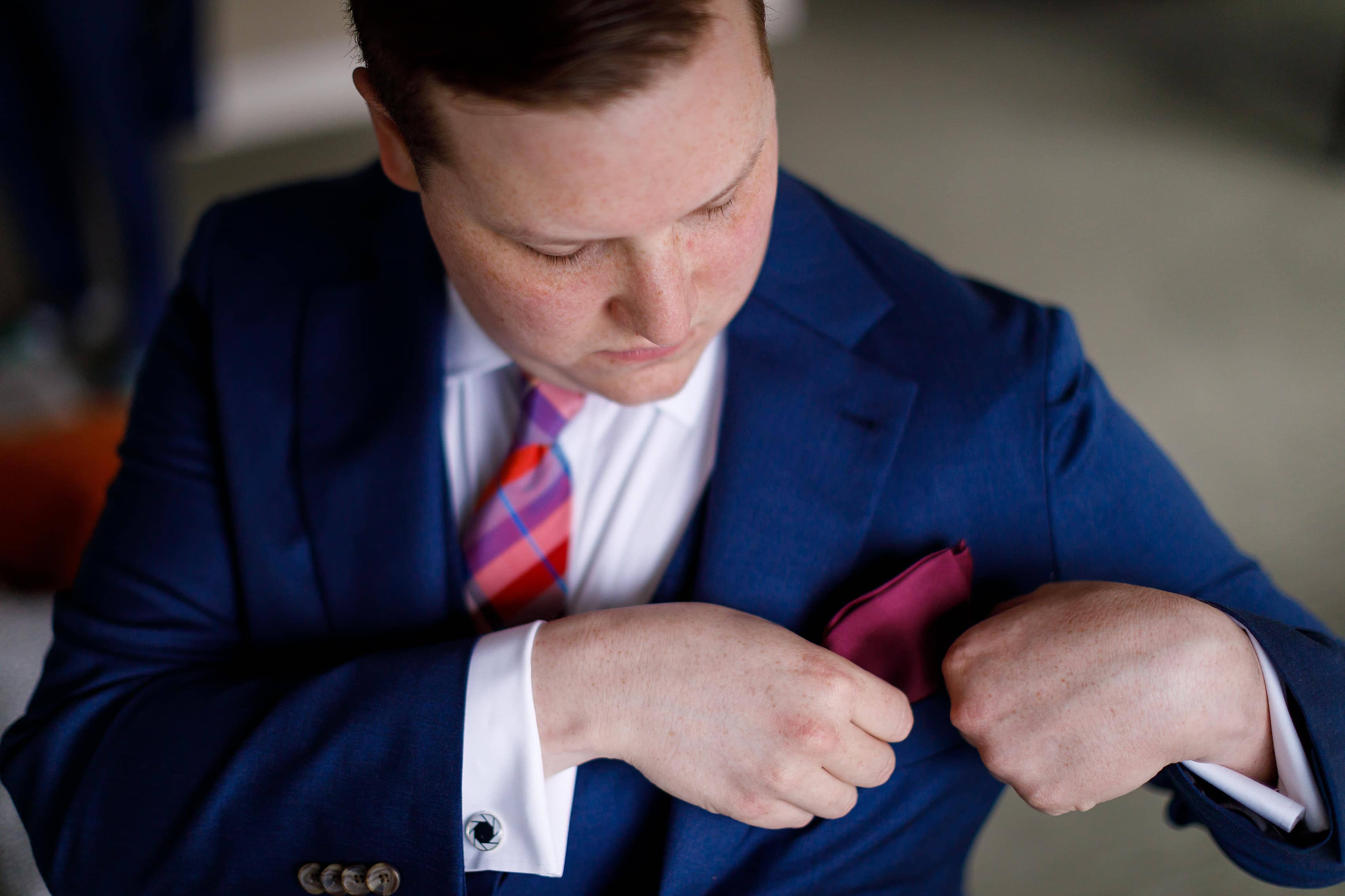 groom puts in pocket square while getting ready for wedding