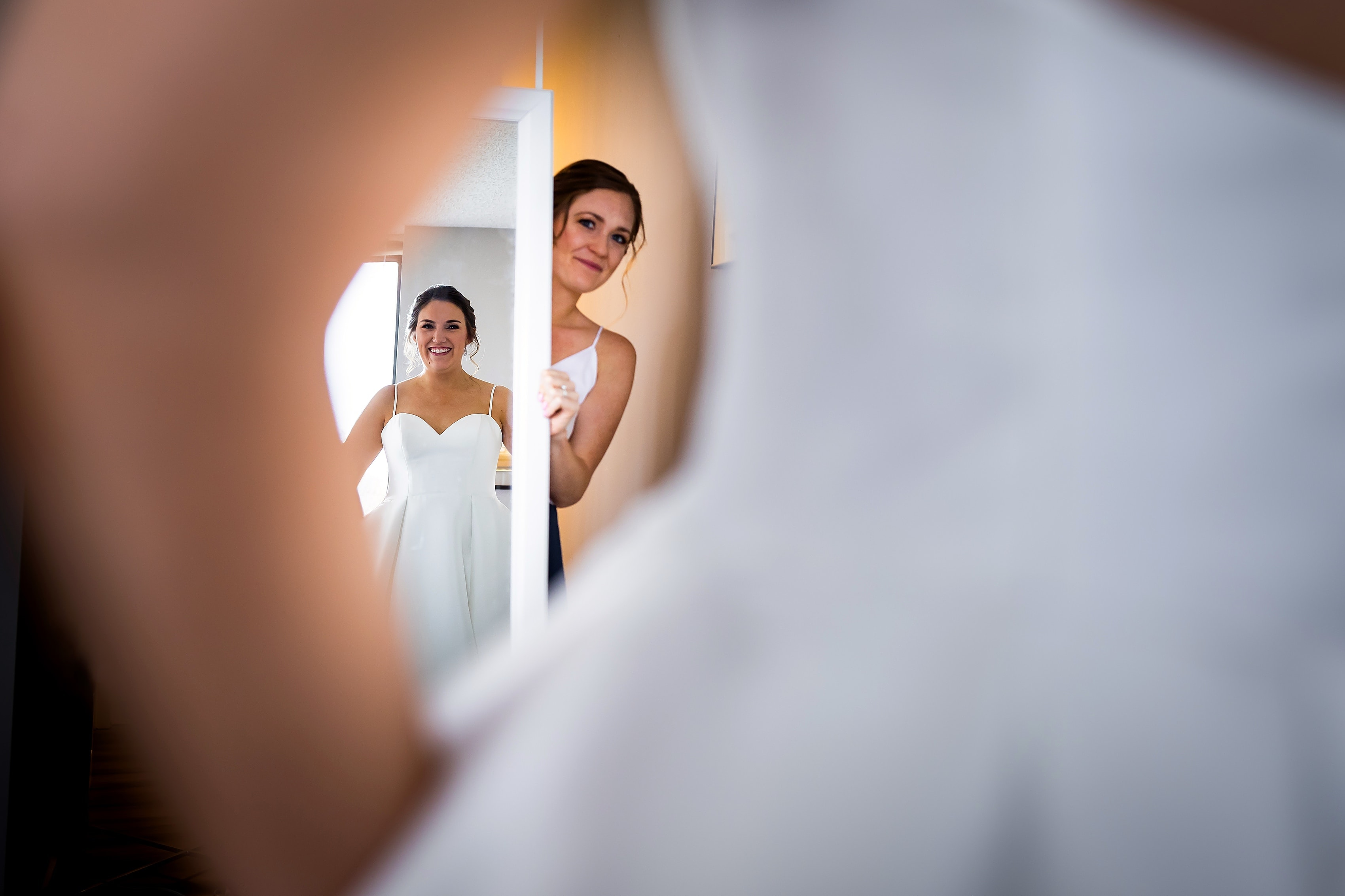 bride looks at herself in the mirror while getting ready for wedding
