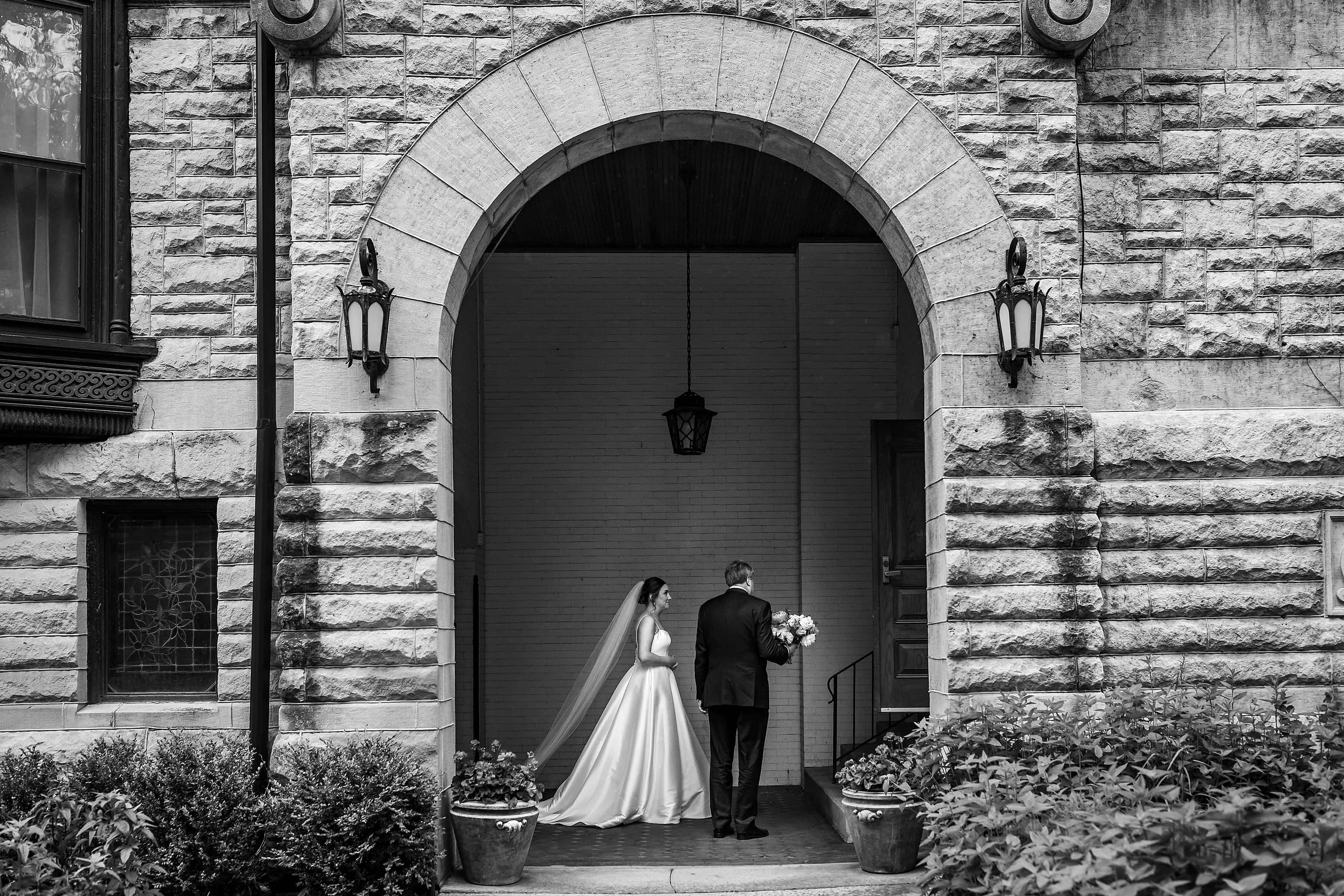 bride and father wait outside Church of our Savior in Chicago before her wedding ceremony