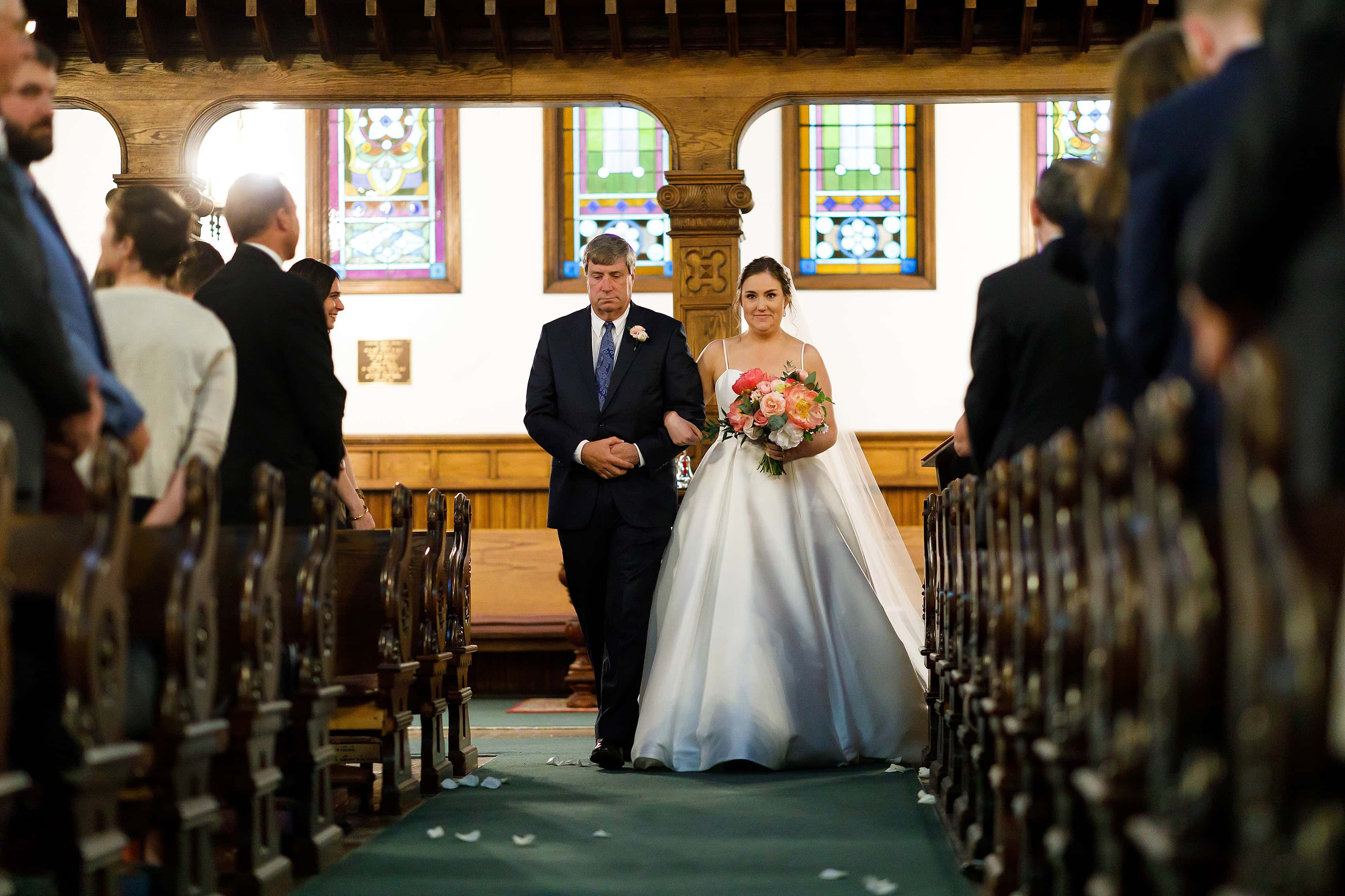bride and father walk down the aisle during wedding ceremony at Church of our Savior