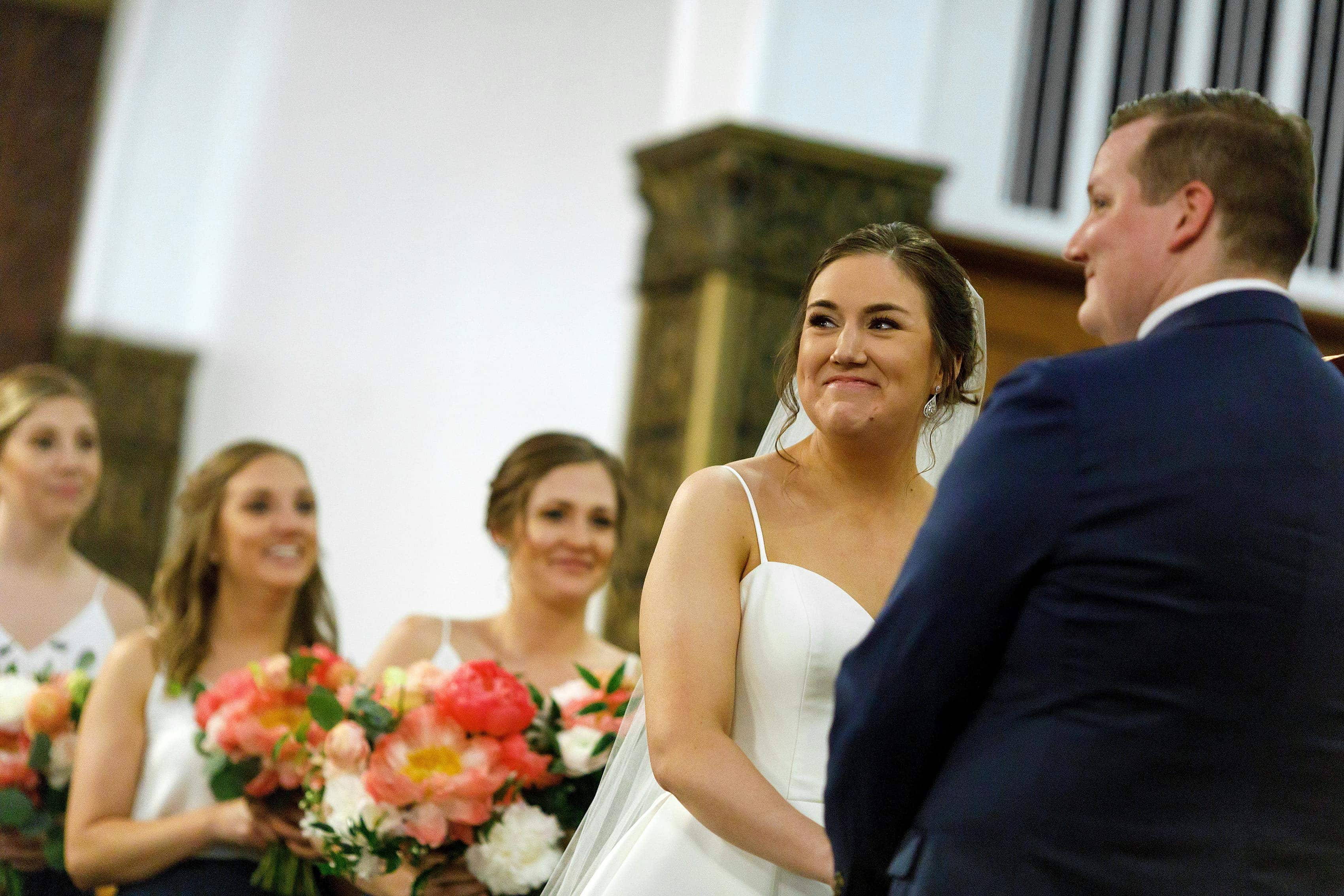 bride and groom smile at guests during wedding ceremony at Church of our Savior