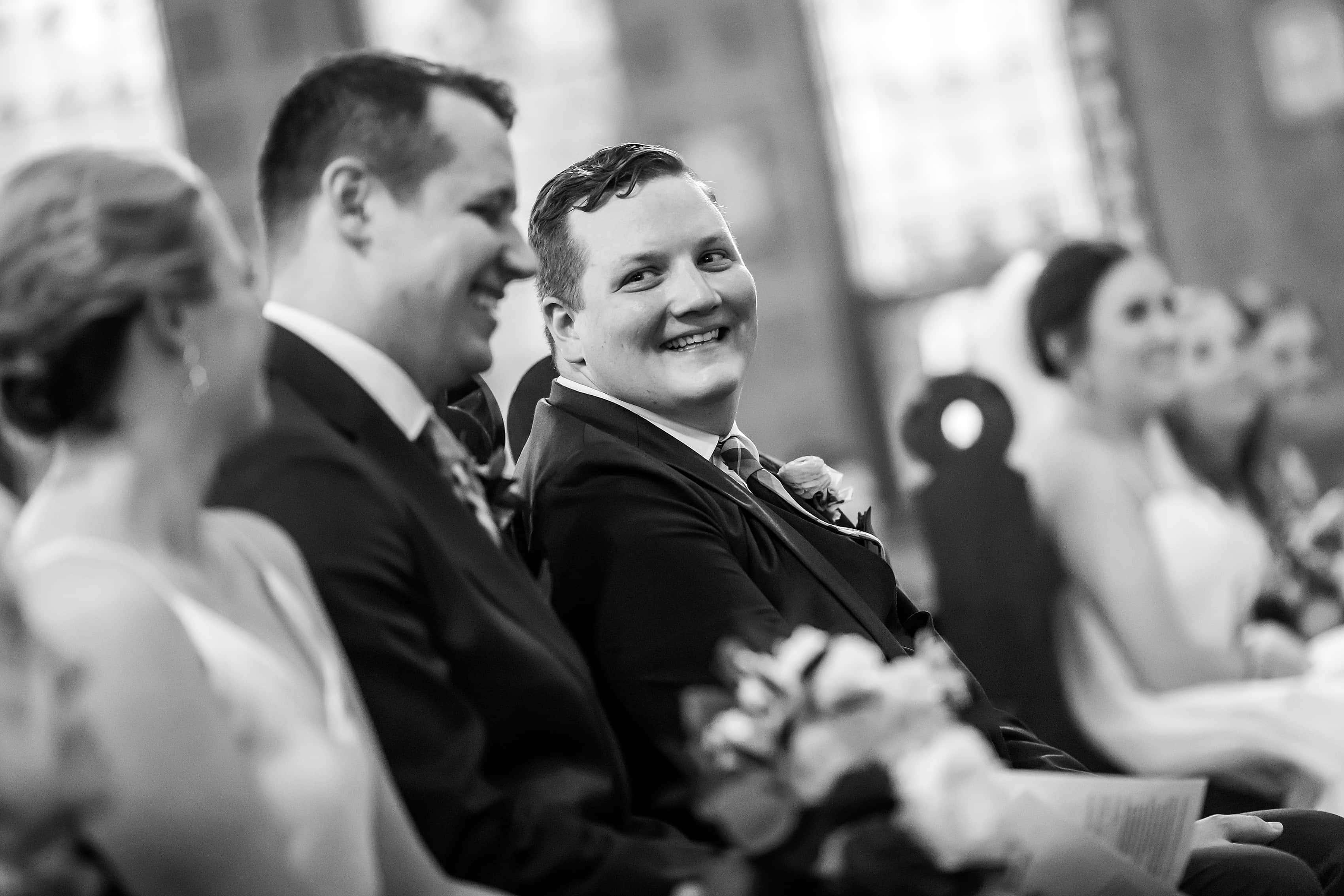 groom smiles at brother during wedding ceremony at Church of our Savior