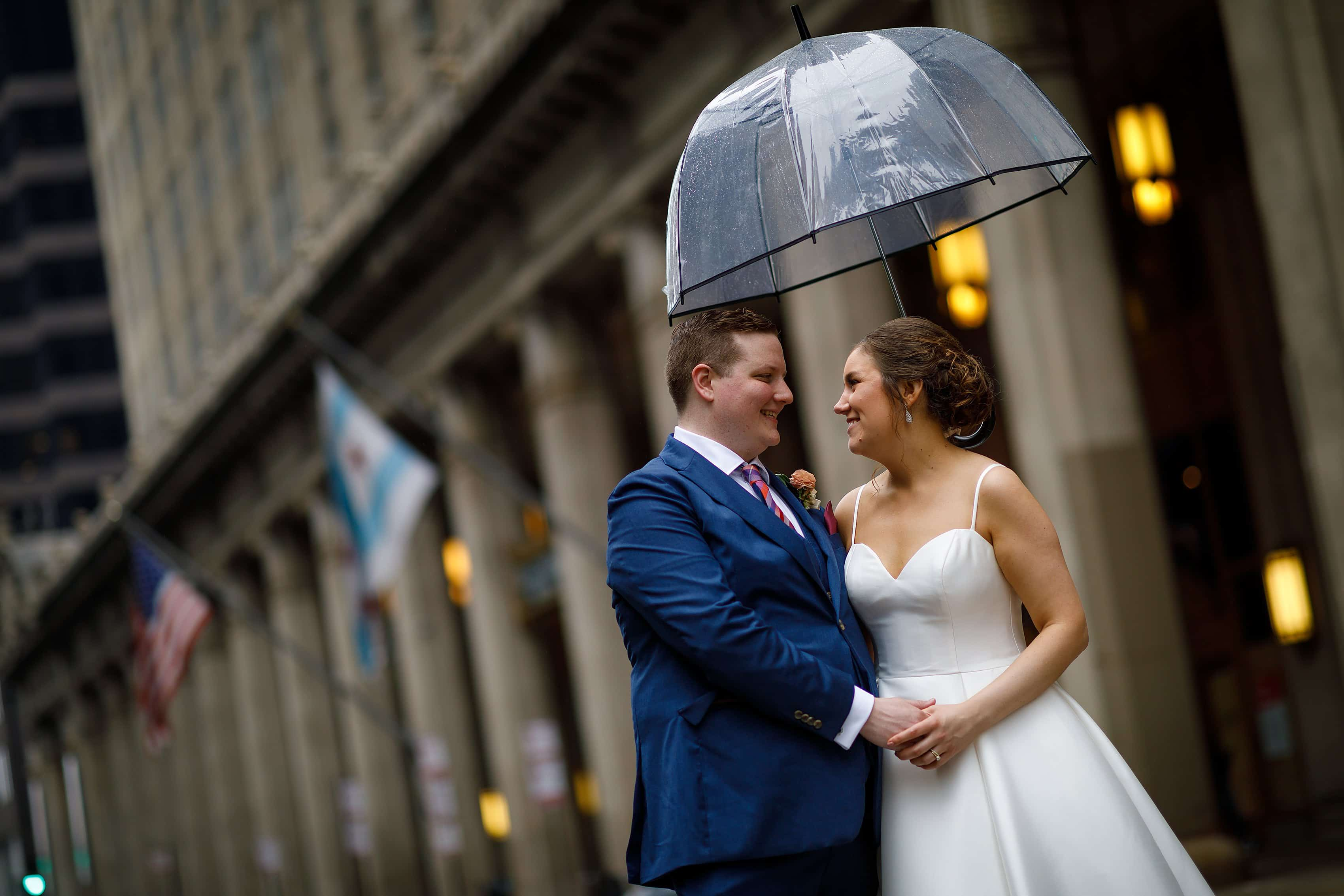 bride and groom under umbrella during wedding portrait at Lyric Opera House in Chicago