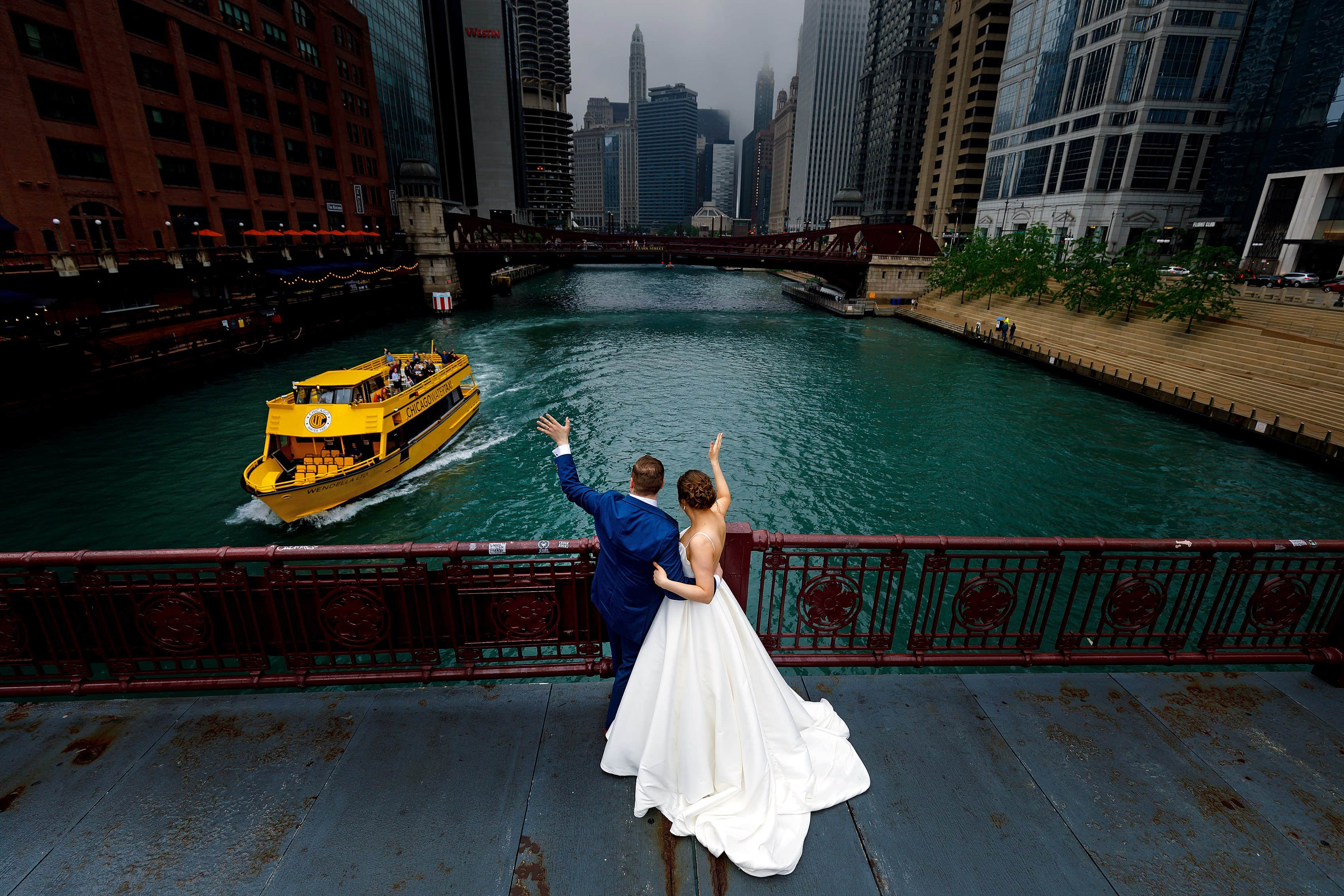 bride and groom wave to water ferry on the Chicago River on the LaSalle Street Bridge