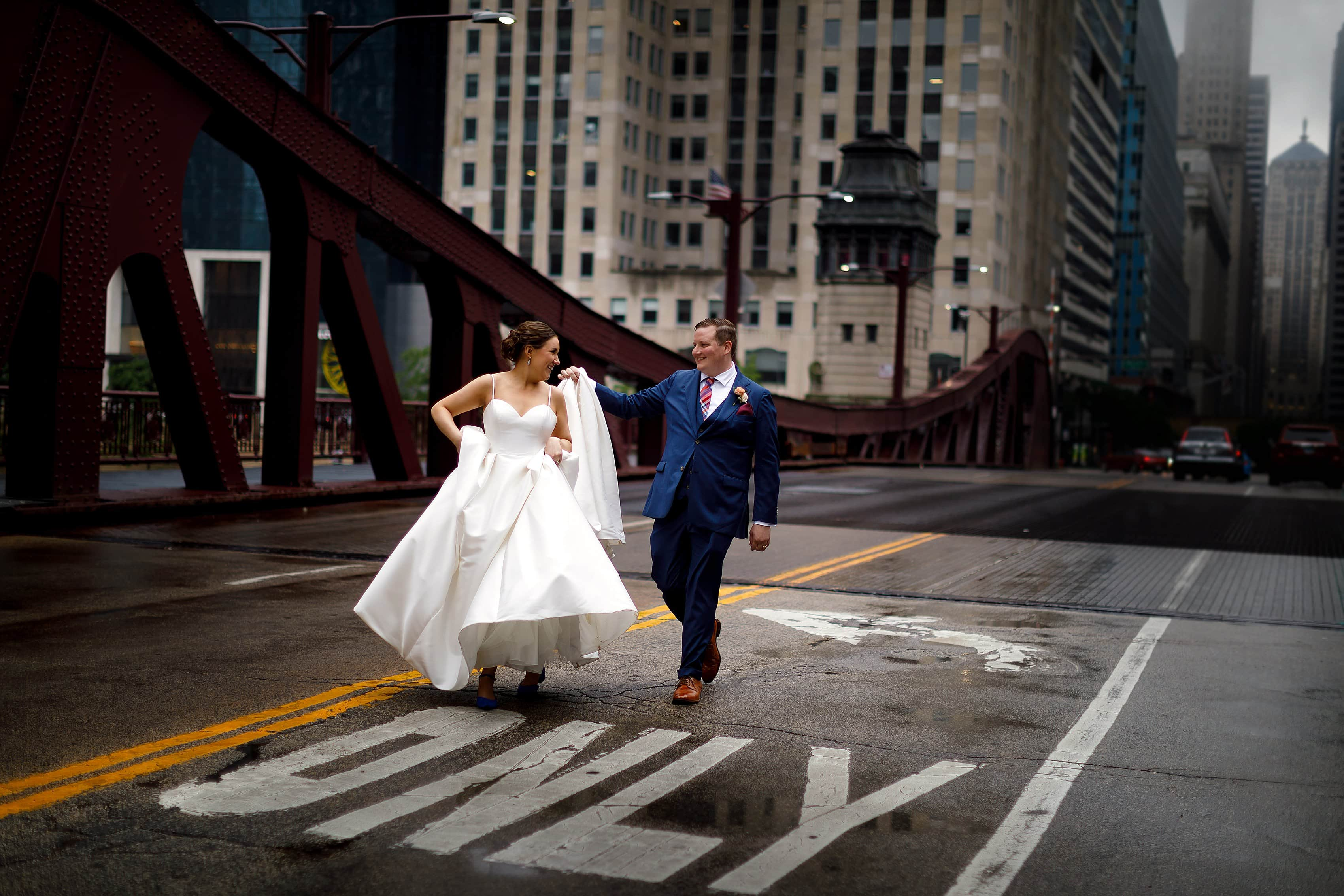 Bride and groom walk across the street for portrait on LaSalle Street Bridge