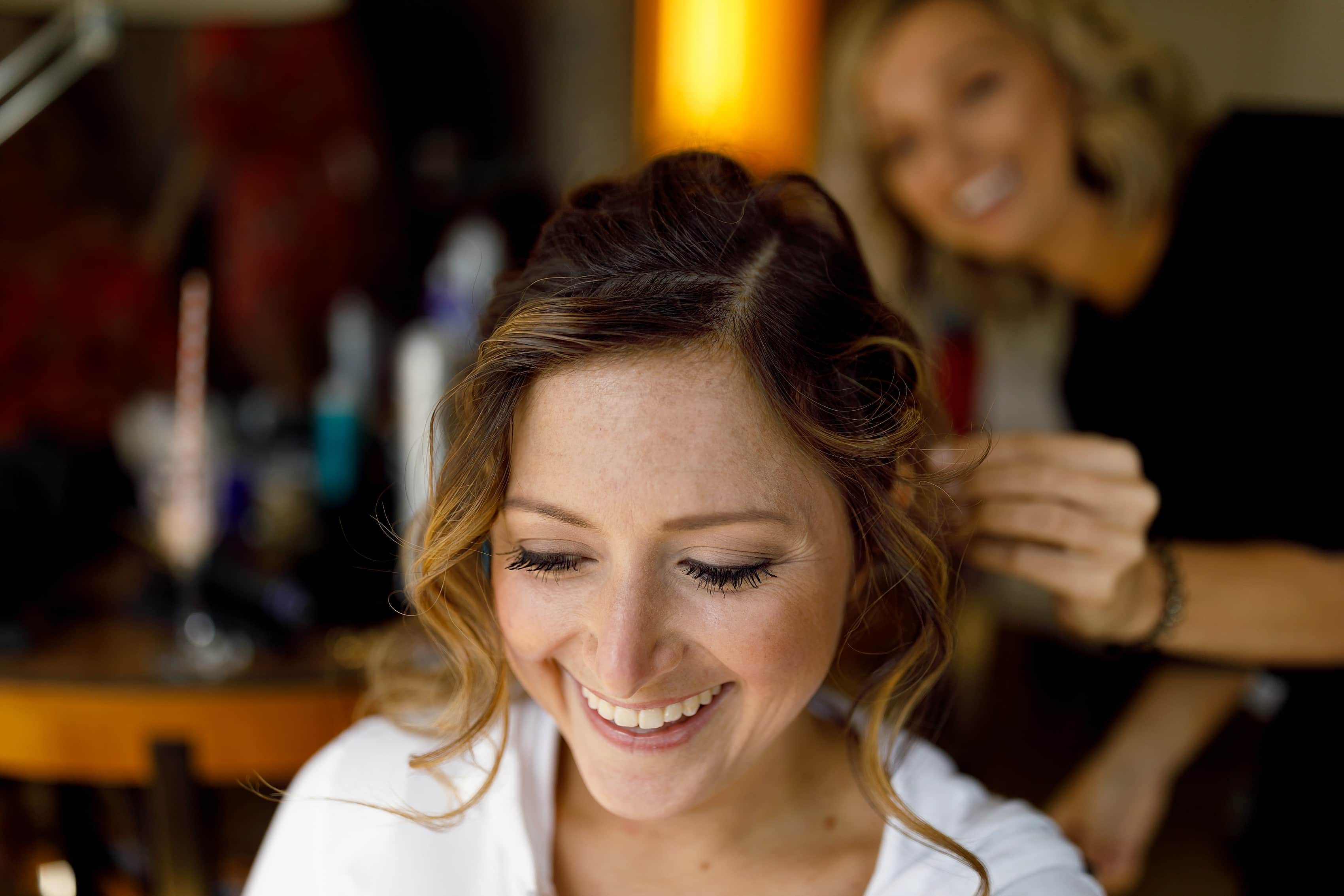 bride smiles while having her hair done before her wedding
