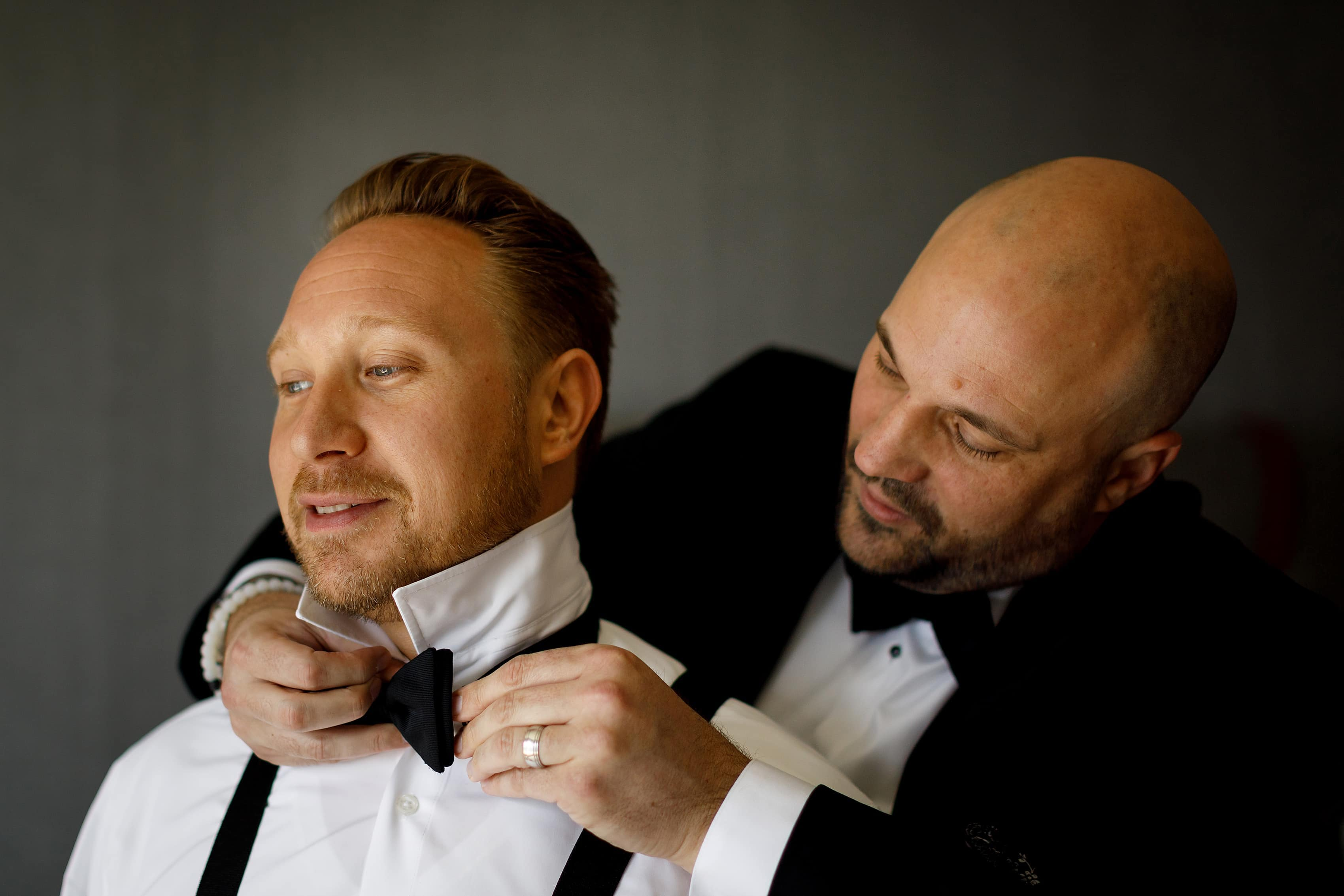 groomsmen helps groom with bowtie while getting ready for wedding
