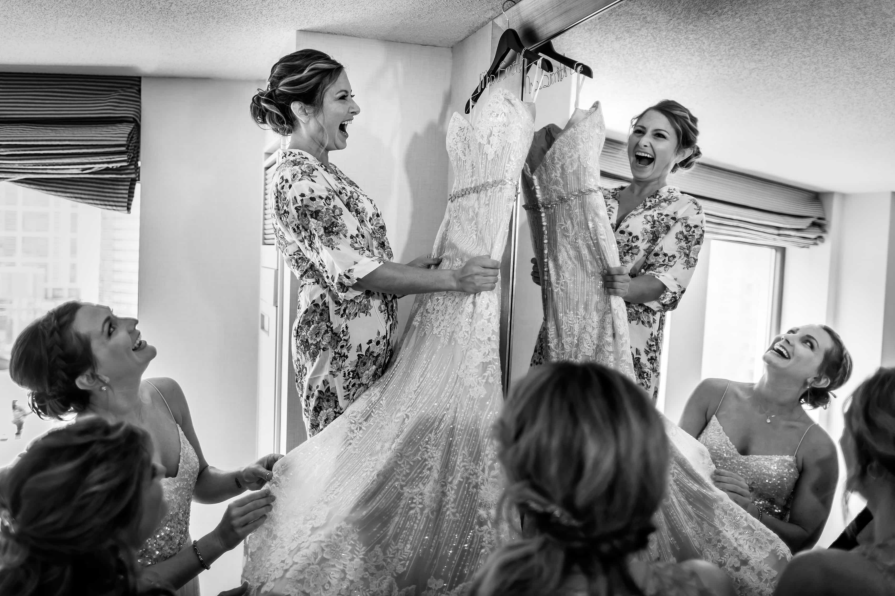 bride screams in excitement before putting on her dress while getting ready for wedding