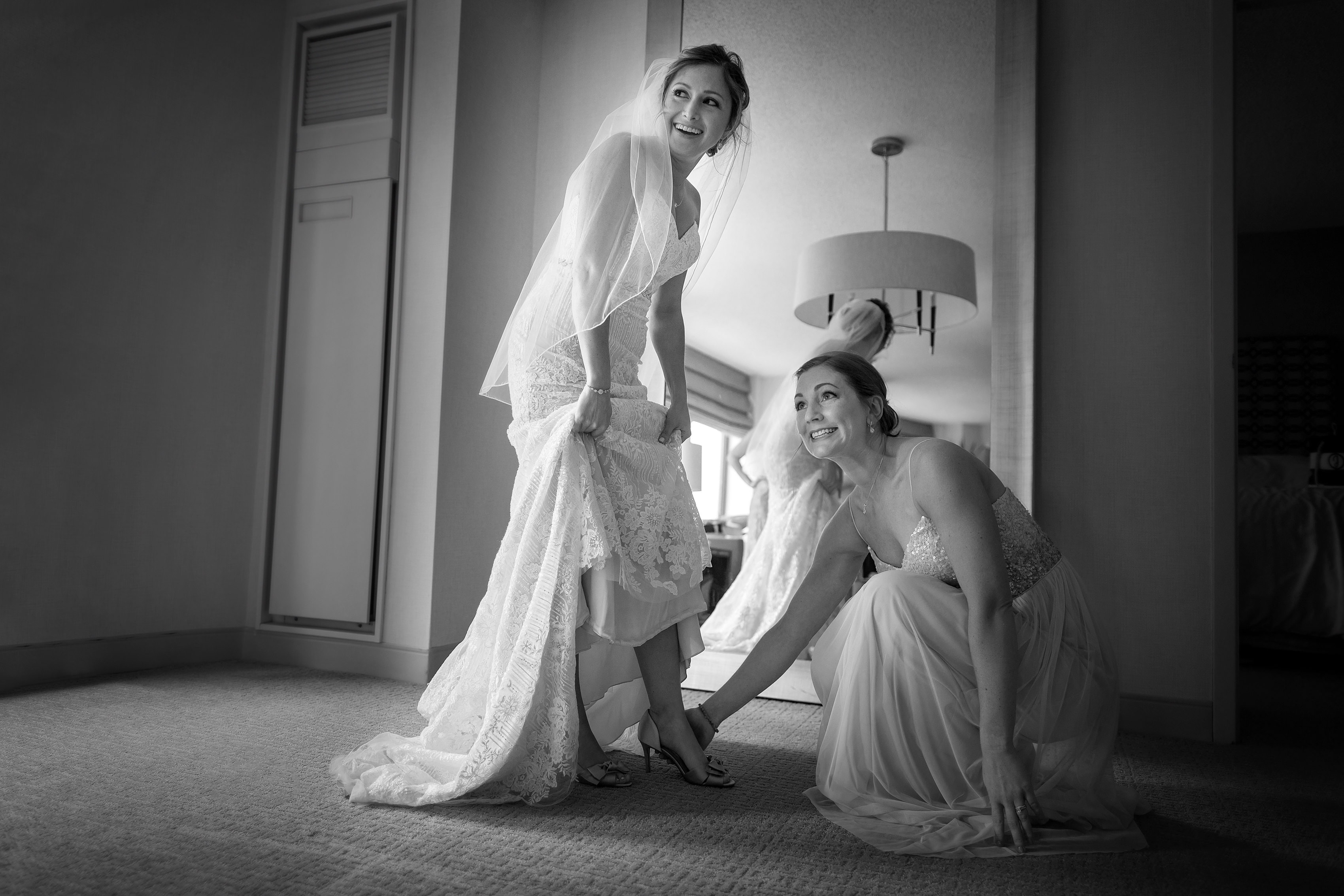 bridesmaid helps bride with shoes while getting ready for wedding at Sheraton Grand hotel in Chicago