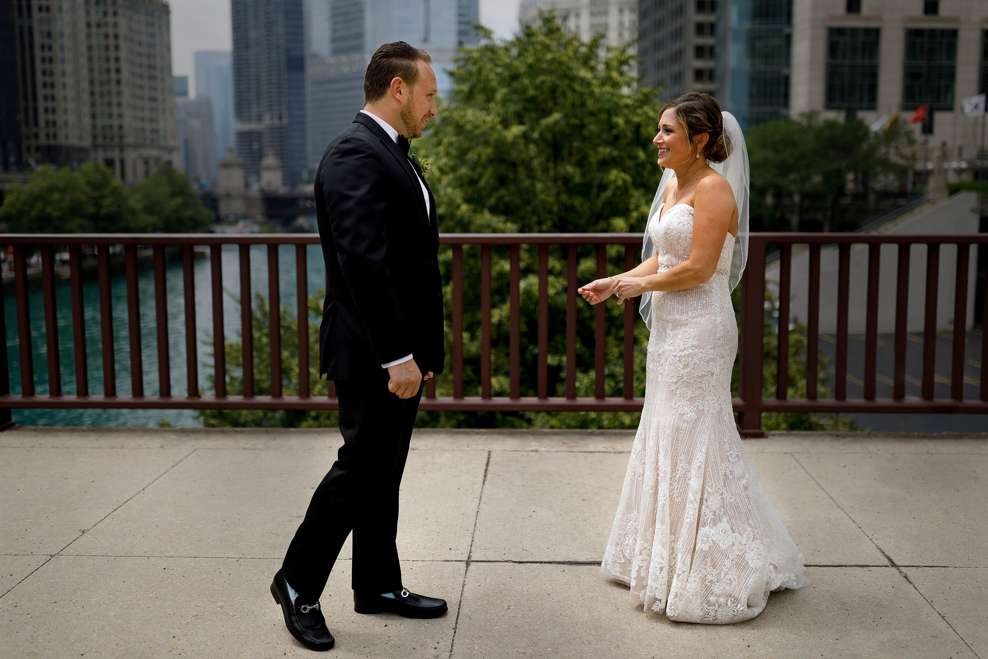 bride and groom see each other for first look with Chicago river in the background
