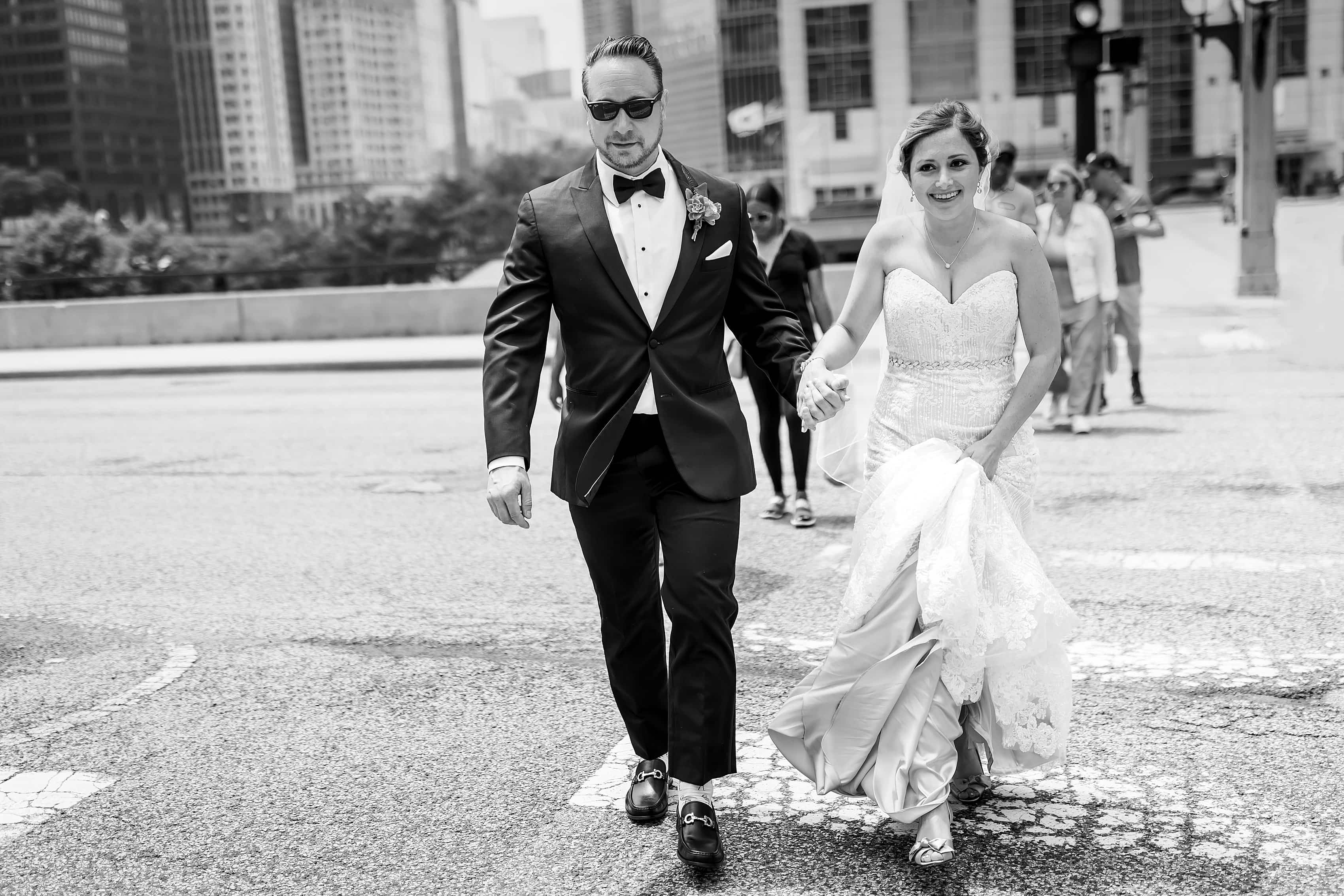 bride and groom walk across the street in black and white