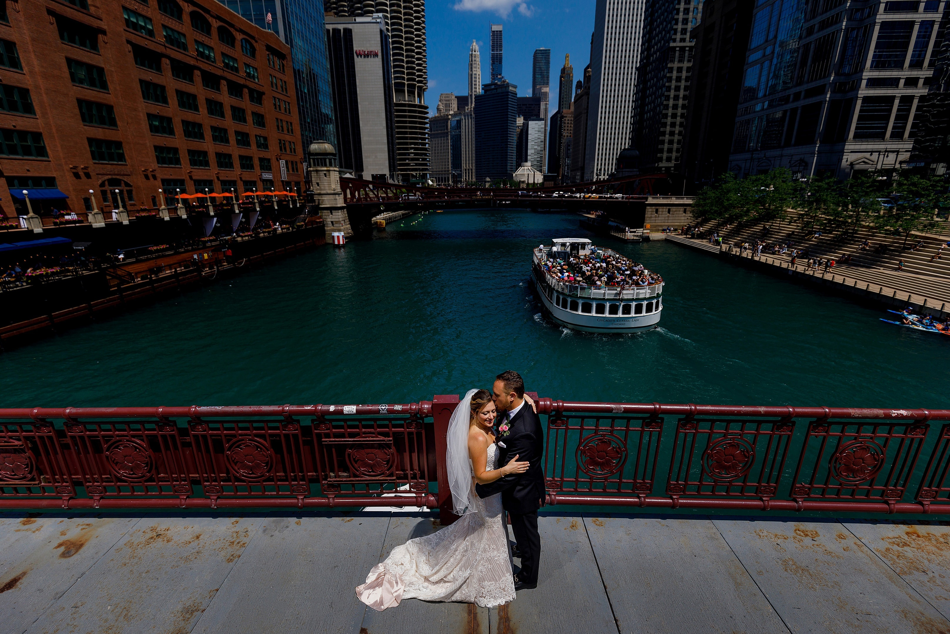 bride and groom pose for a portrait on LaSalle Street Bridge in downtown Chicago