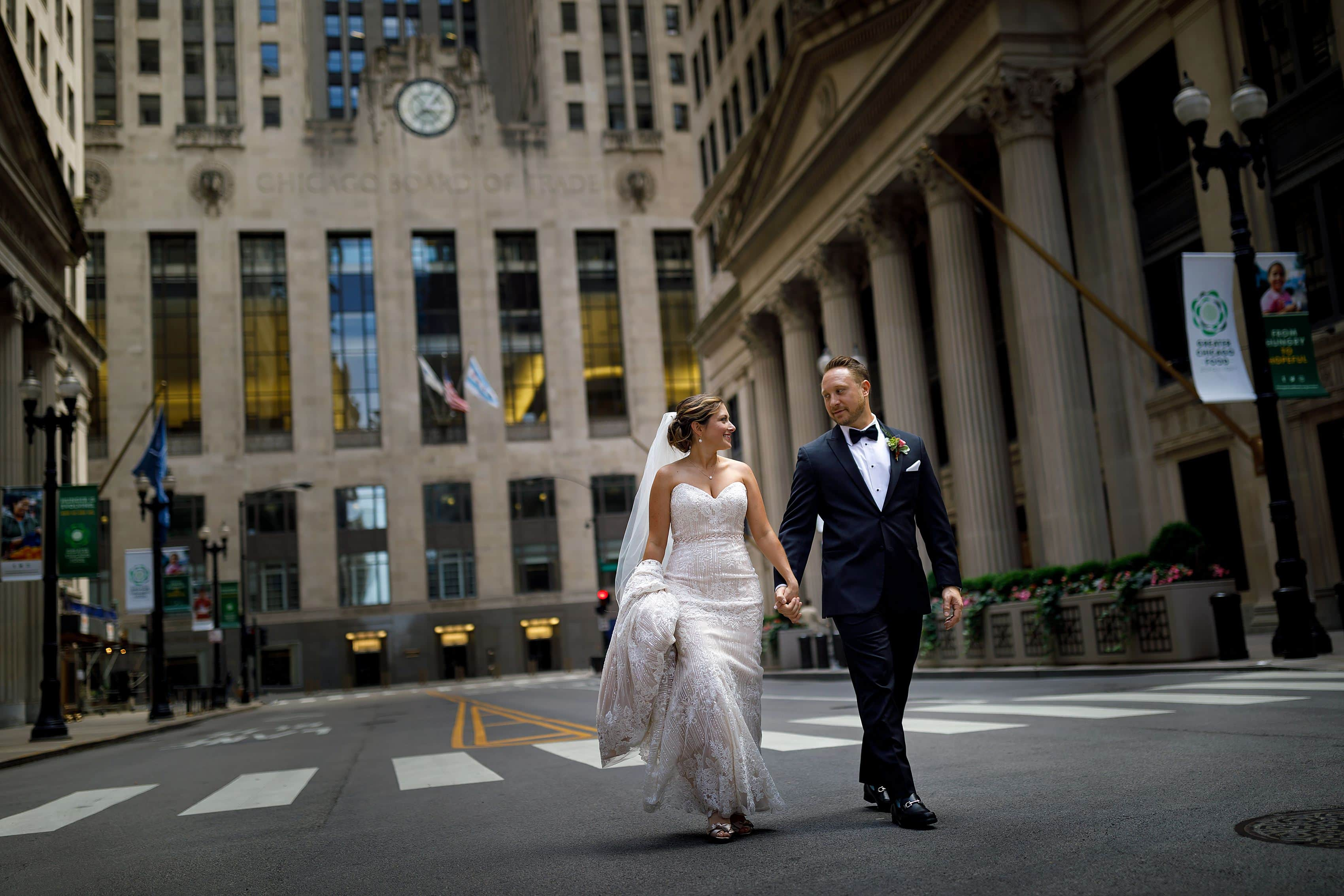 bride and groom walk down LaSalle Street in front of the Chicago Board of Trade building