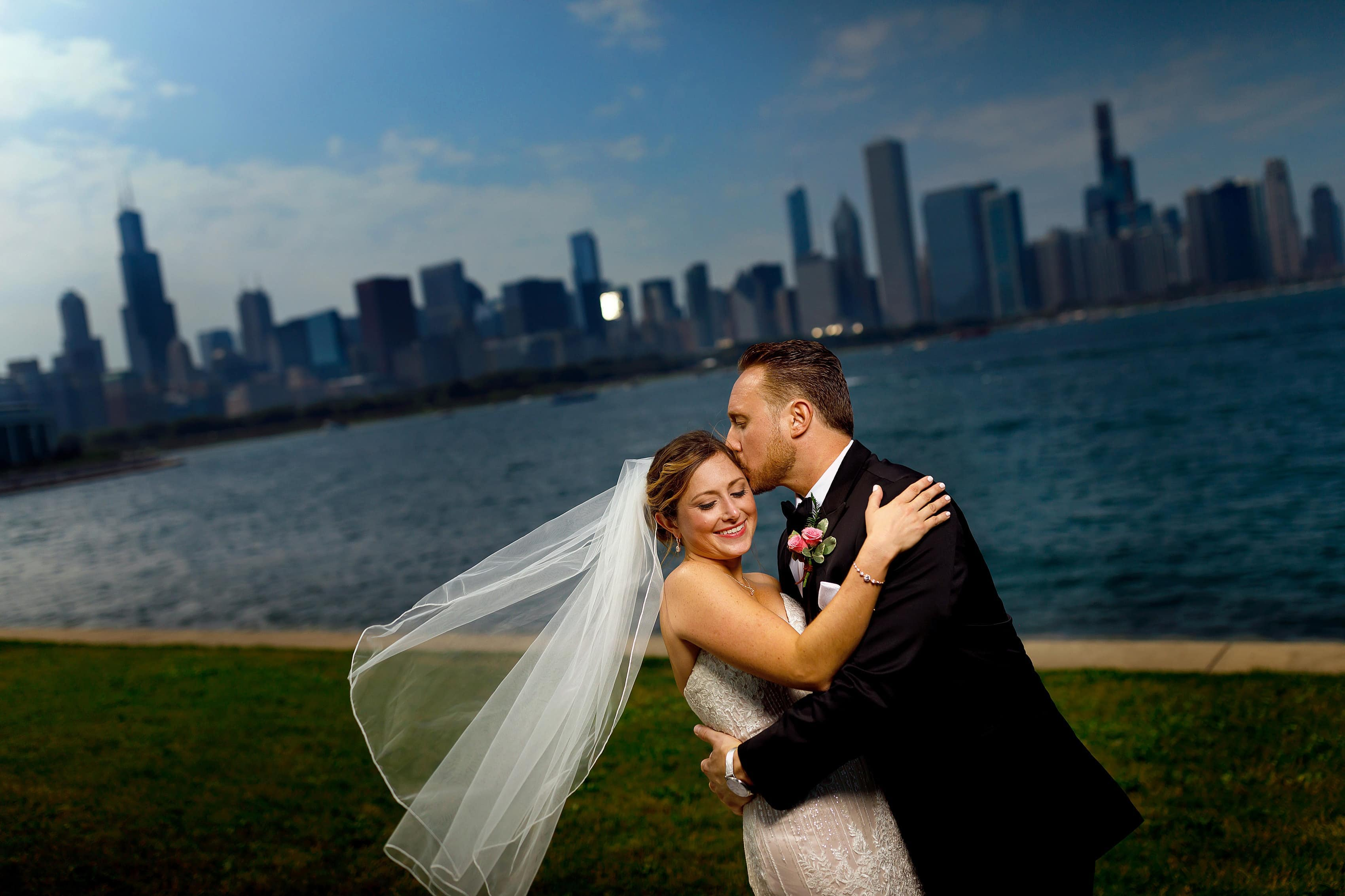 bride and groom wedding portrait with full Chicago Skyline in the background from Adler Planetarium and Museum campus