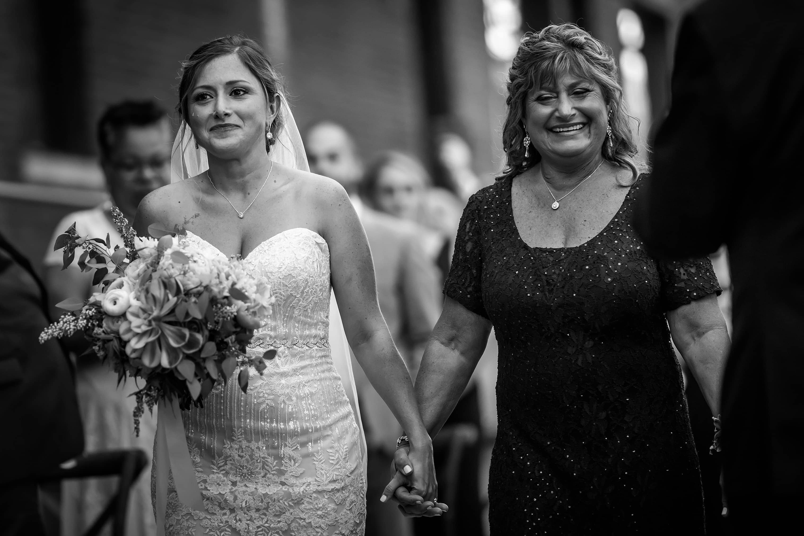 bride walks down the aisle with her mother during wedding ceremony at Bridgeport Art Center Sculpture Garden in Chicago