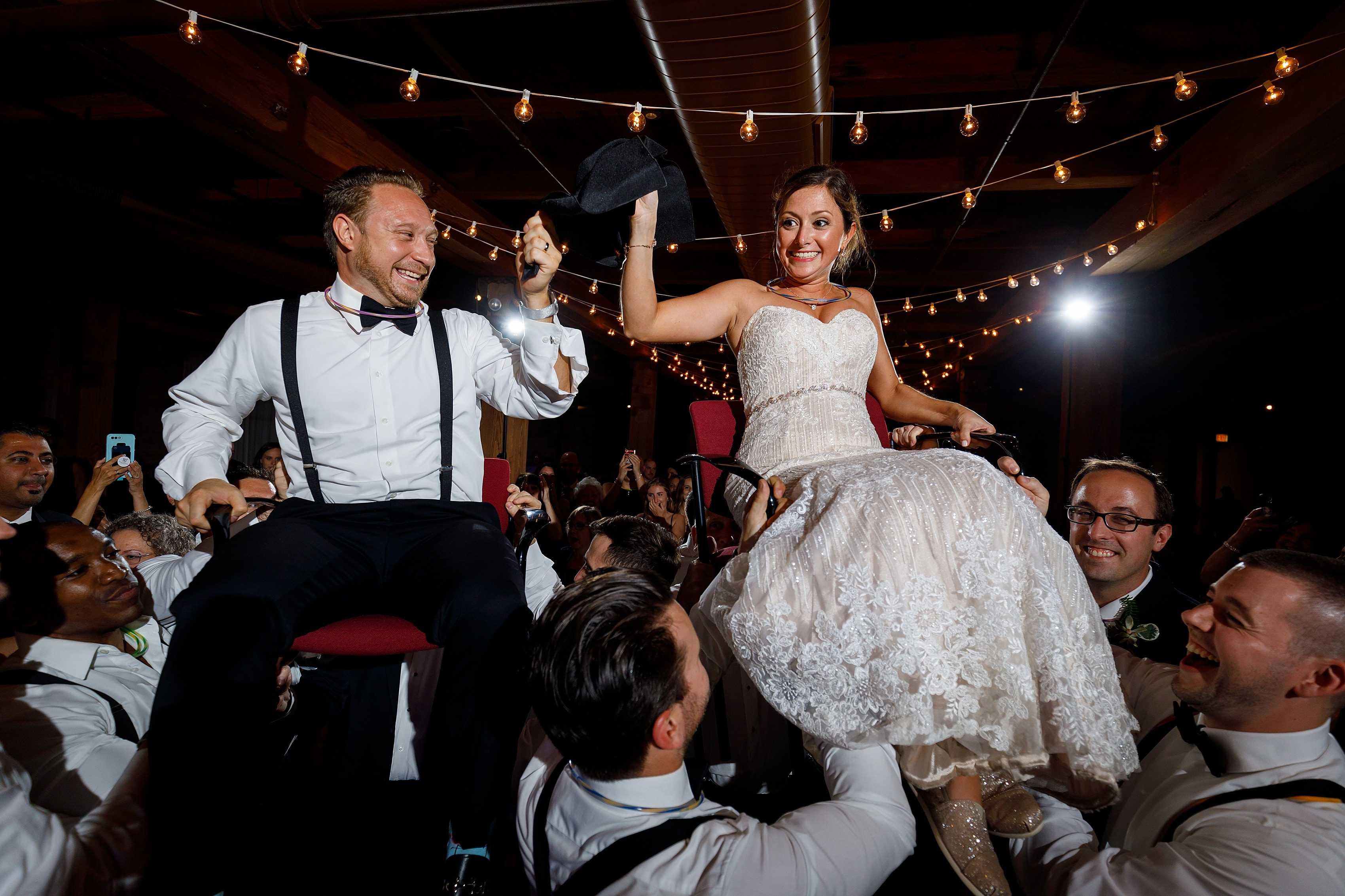 bride and groom are lifted onto chairs for the hora during wedding reception at Bridgeport Art Center Sculpture Garden in Chicago