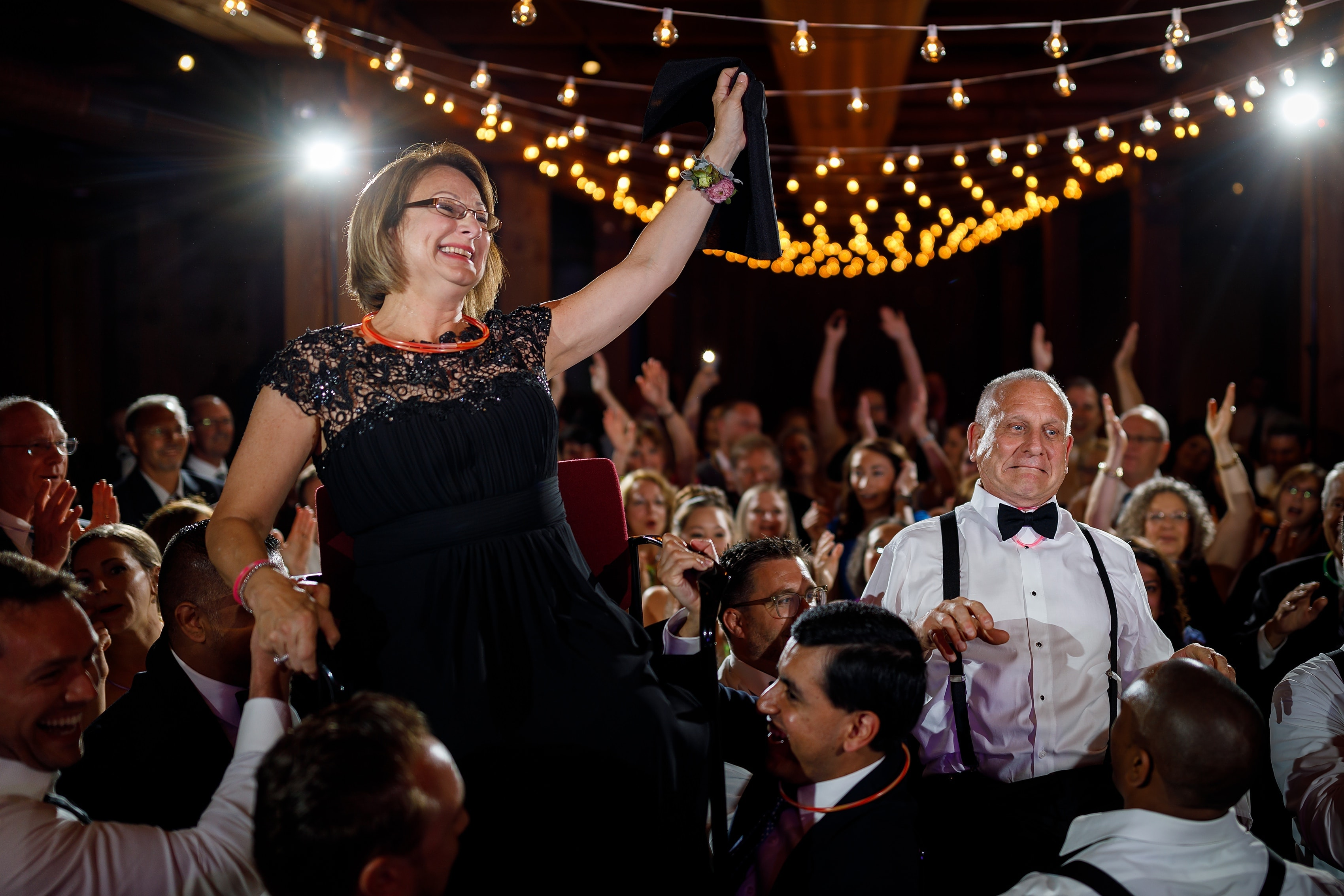 parents of the groom are lifted onto chairs for the hora during wedding reception at Bridgeport Art Center Sculpture Garden in Chicago