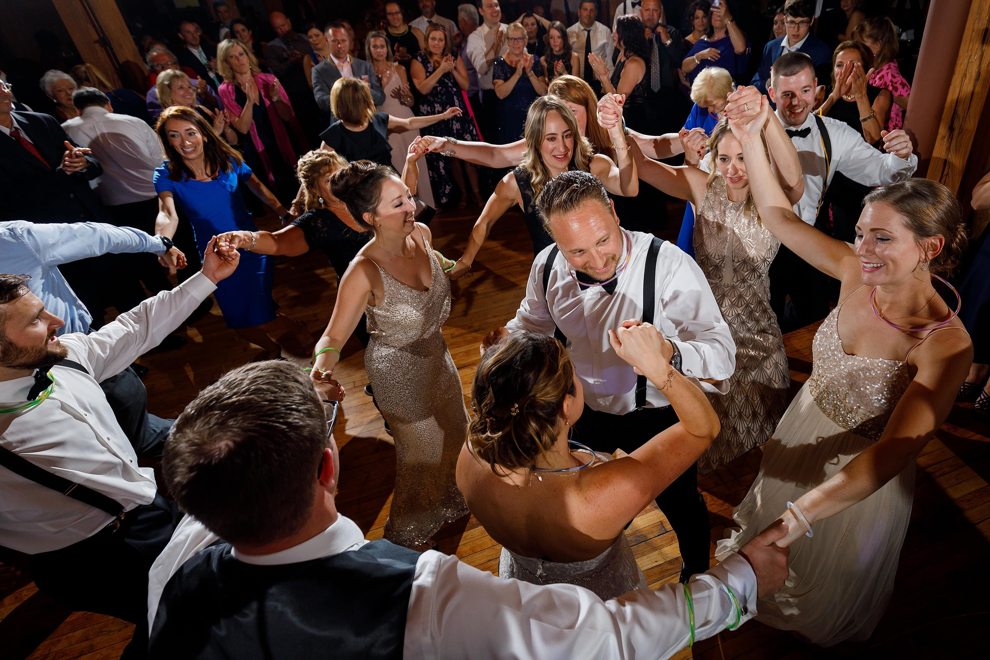 wedding guests dance around the couple during wedding reception at Bridgeport Art Center Sculpture Garden in Chicago
